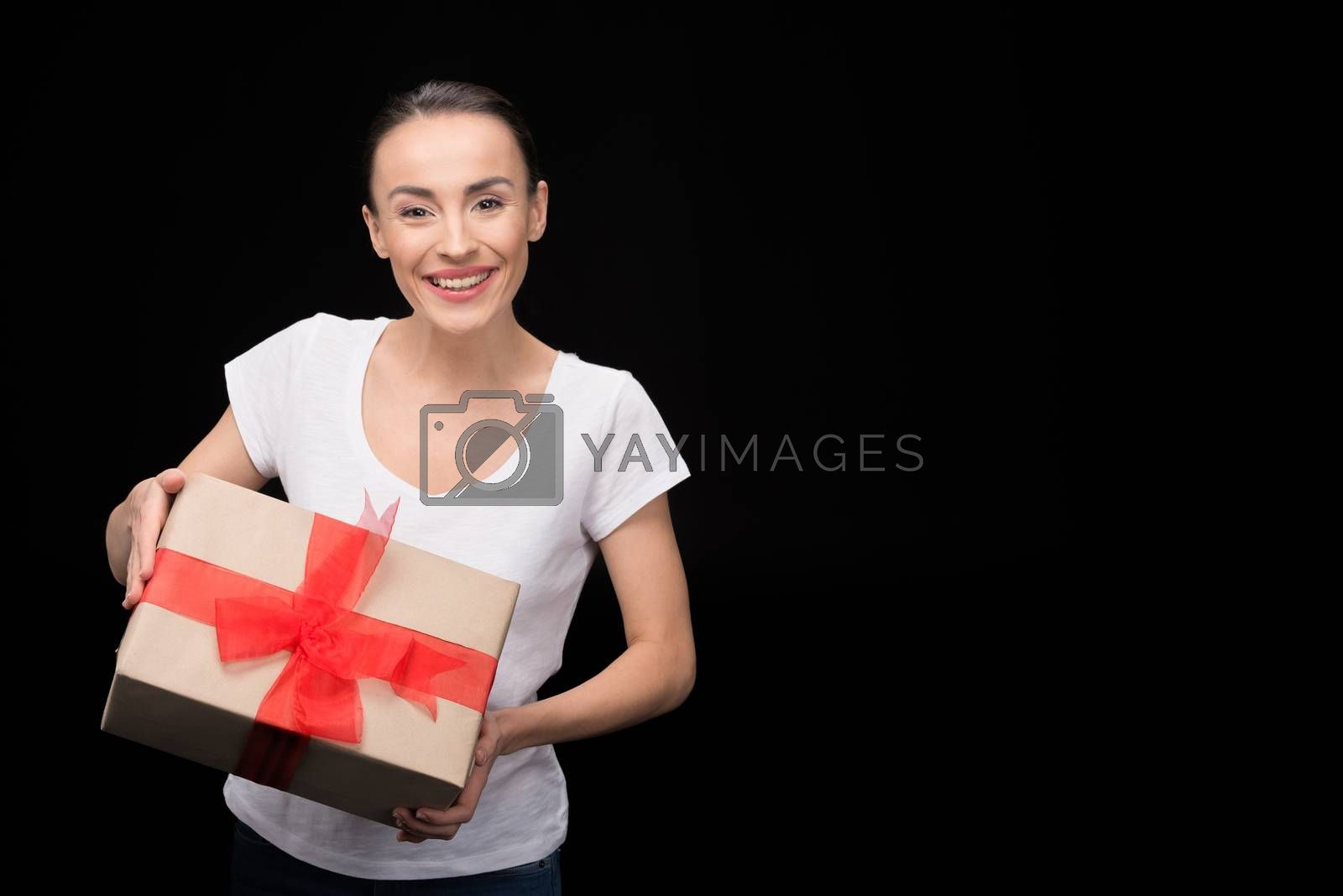 portrait of smiling woman holding gift in hands and looking to camera on black, international womens day concept