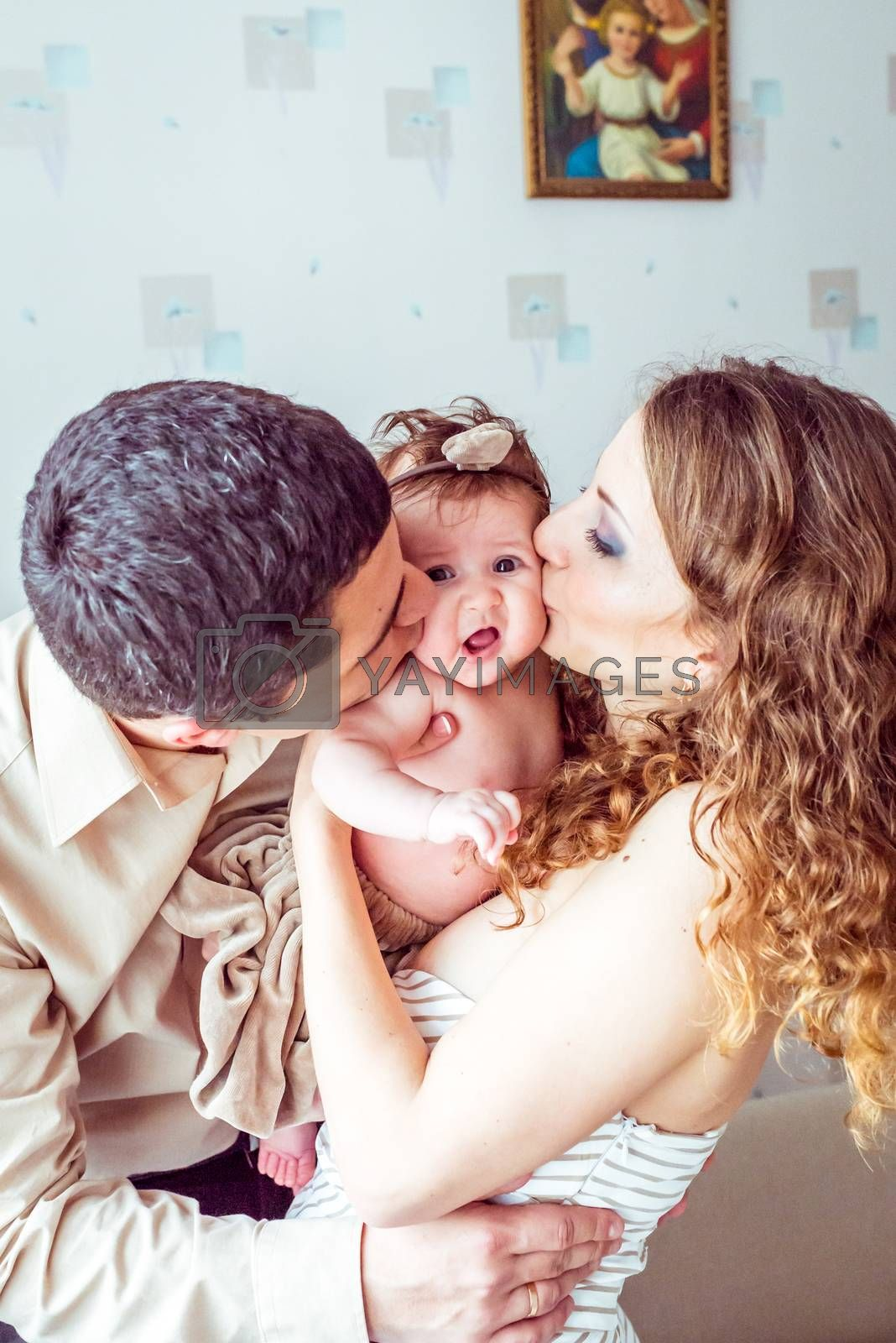 Happy parents kiss the baby in her arms in the room