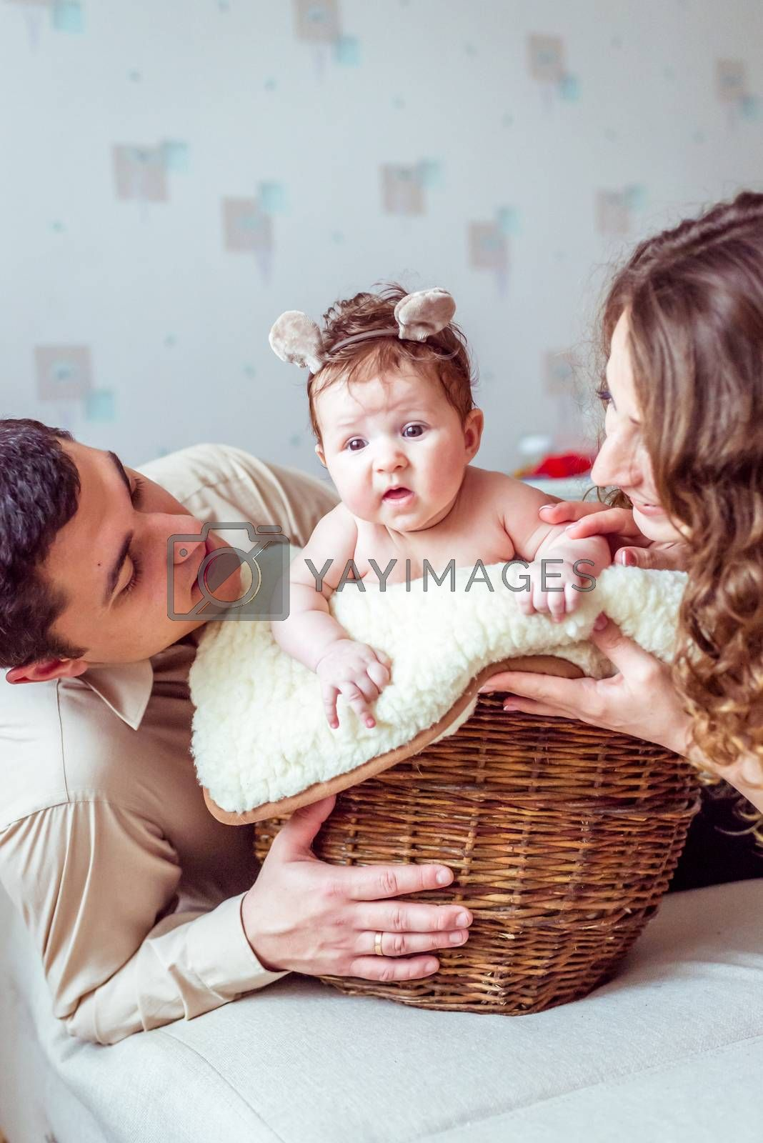 naked baby with her parents sitting in the wicker basket on the white soft blanket