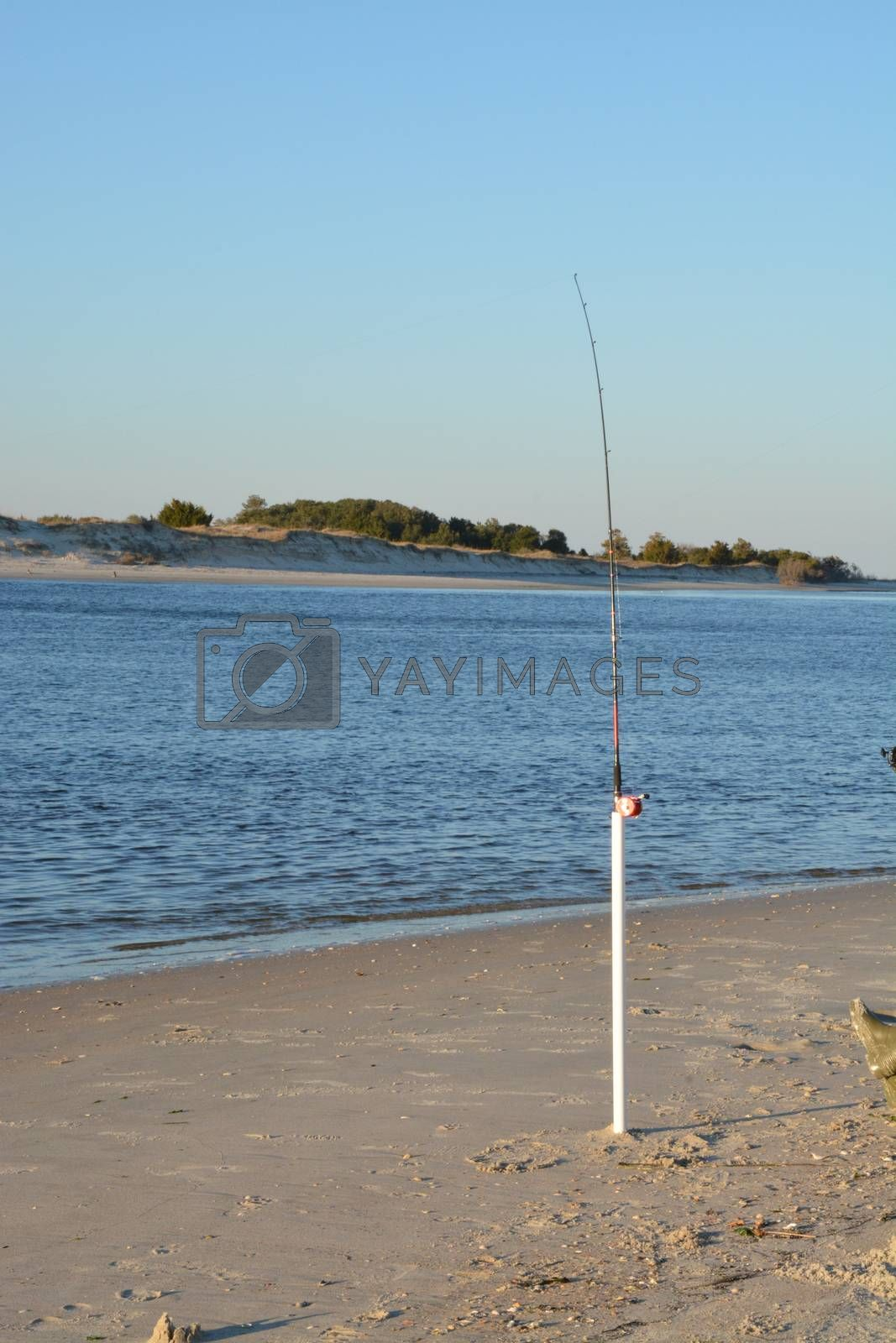 A view of the shore around the north end of Carolina Beach with a fishing pole suck in the ground.