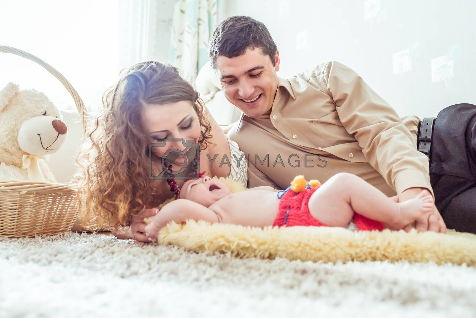naked baby with her parents lying on soft blanket in the room