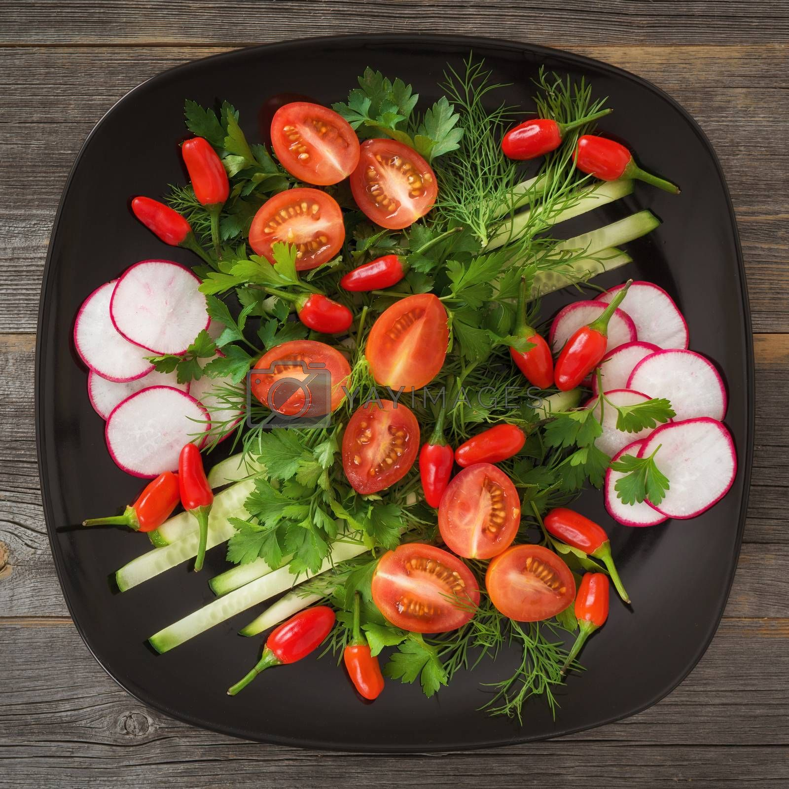 Greens and vegetable salad on a black ceramic plate in style a rustic