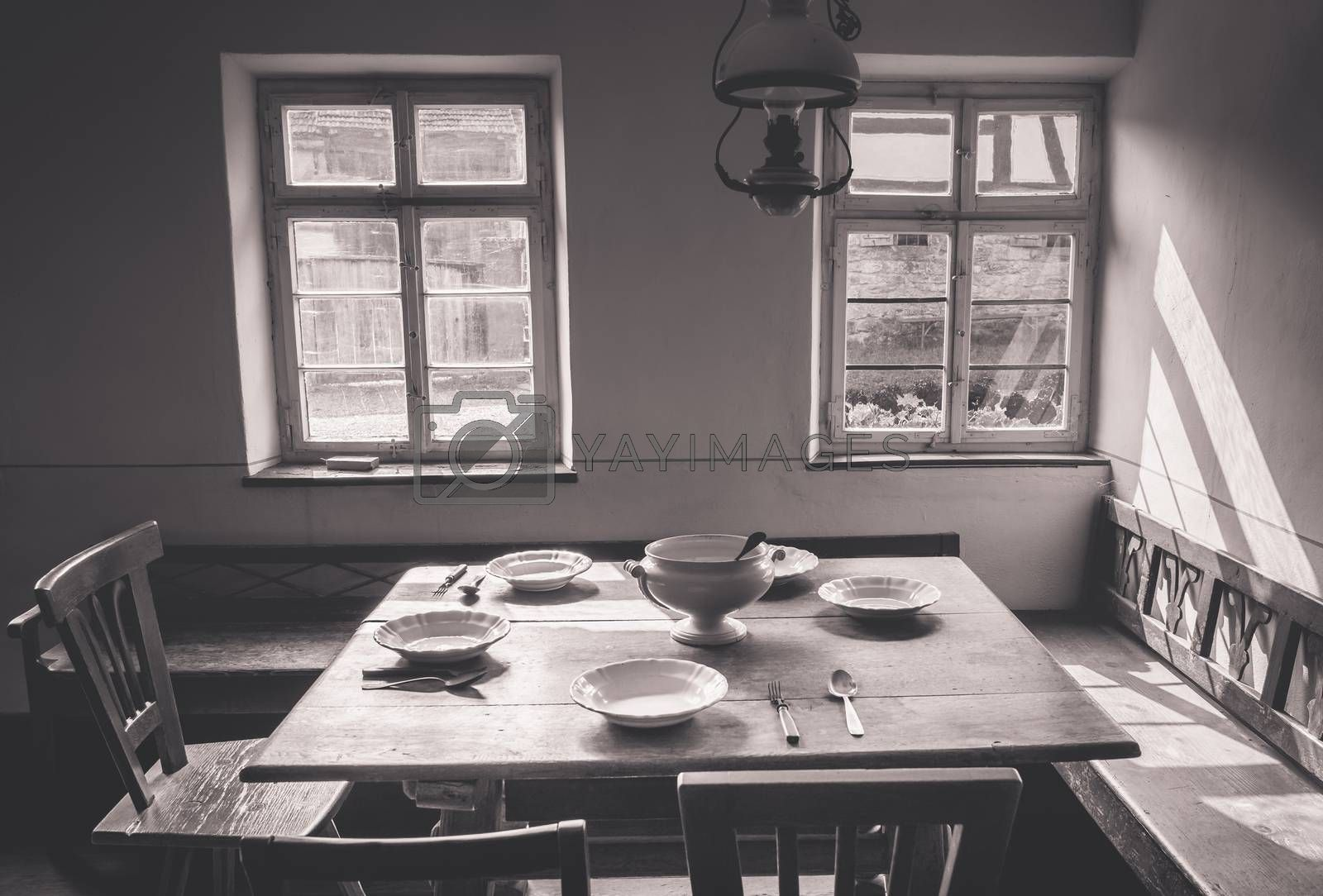 Rustic dining room in vintage settings with wooden table, chairs and benches. Old dishes and tableware are placed on the table.