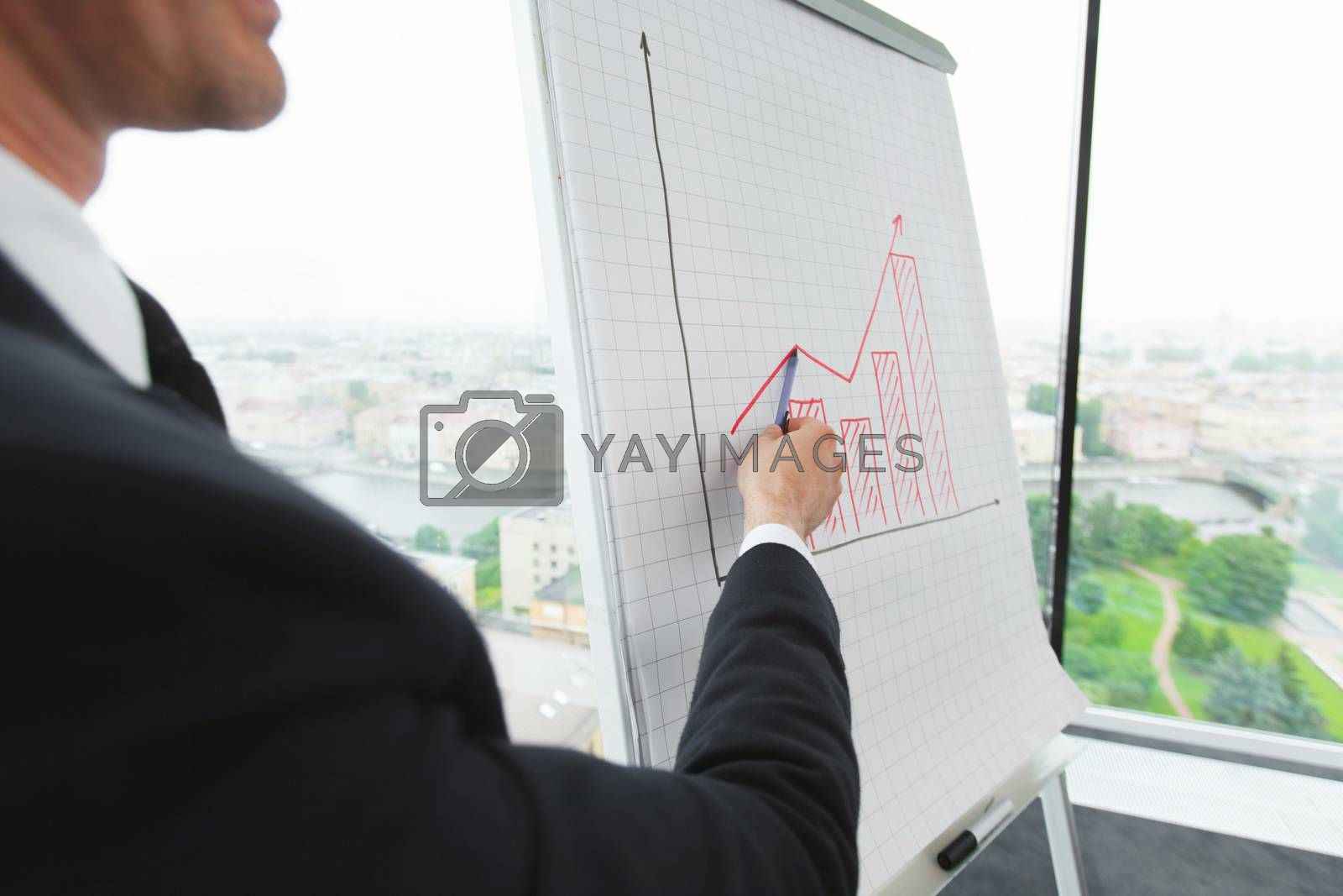 Business man pointing at financial graph showing successful growth