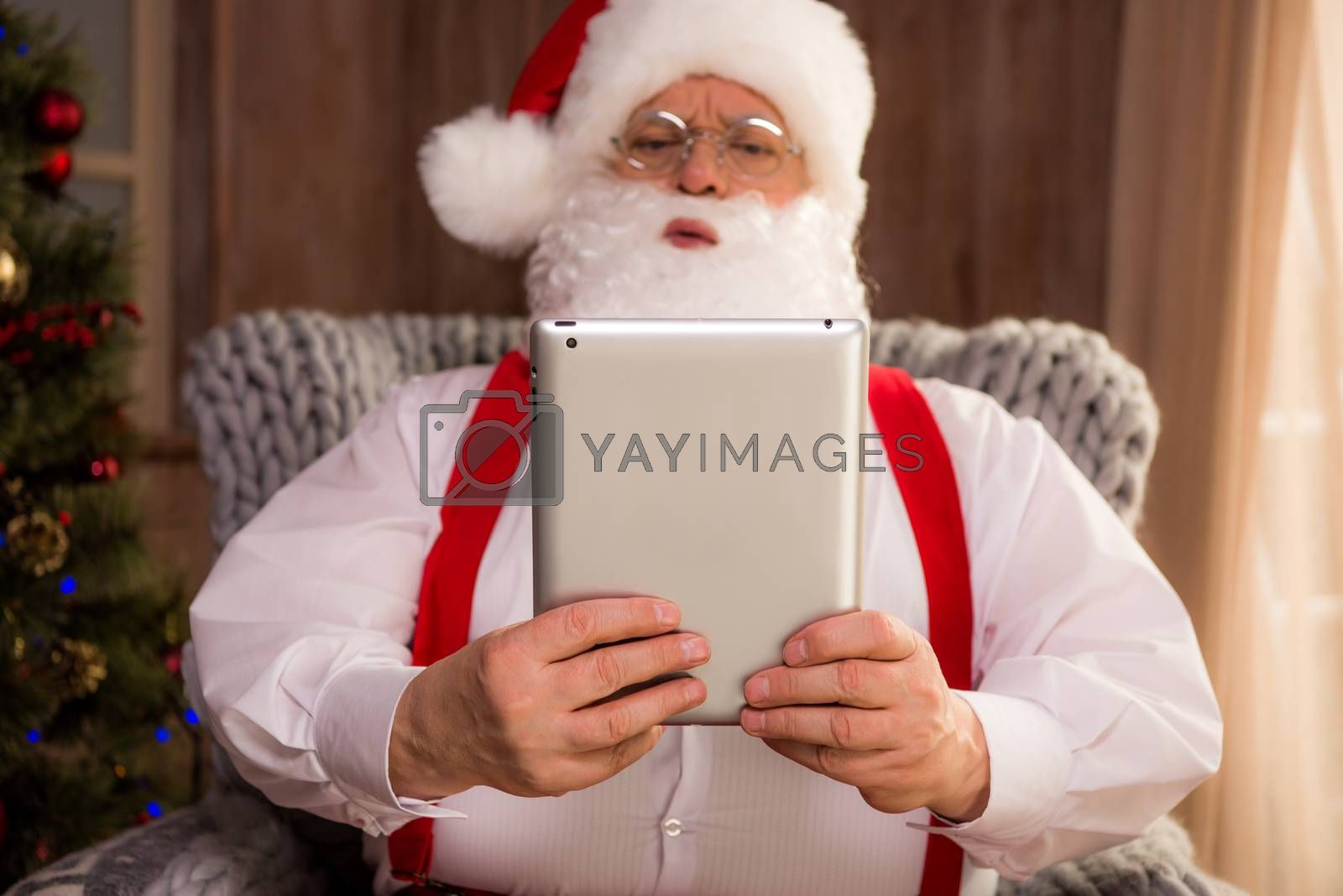 Portrait of Santa Claus sitting in armchair and using digital tablet