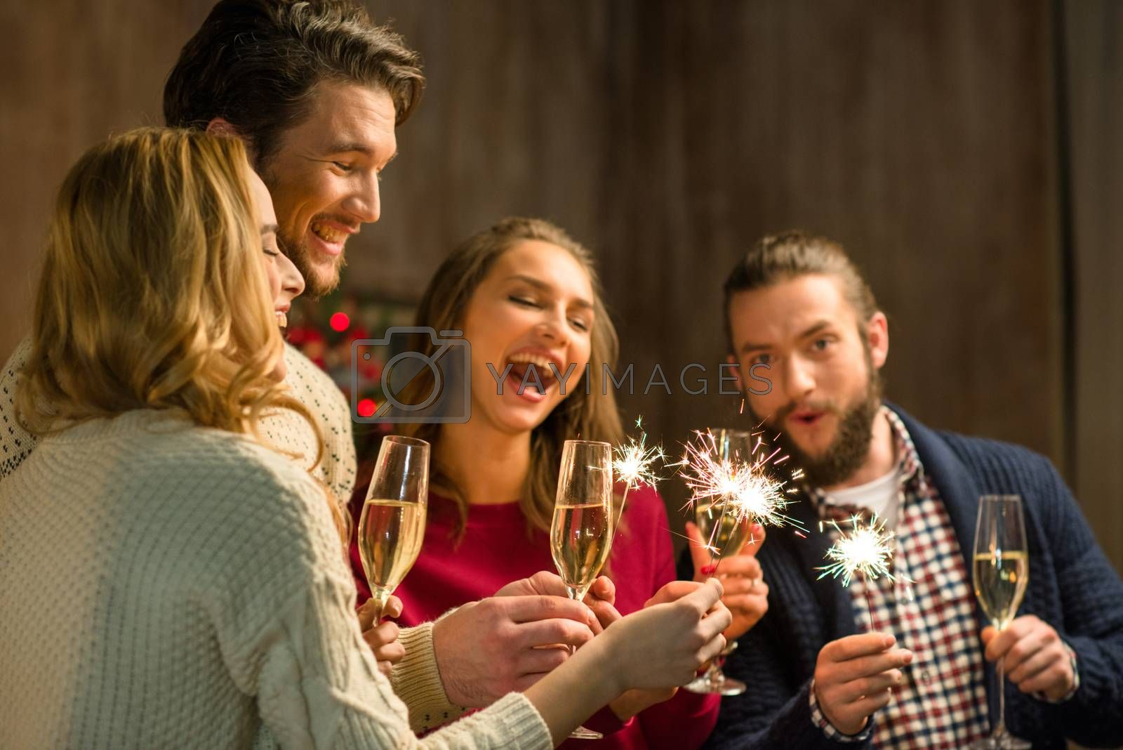 Group of happy people with glasses of champagne and sparklers