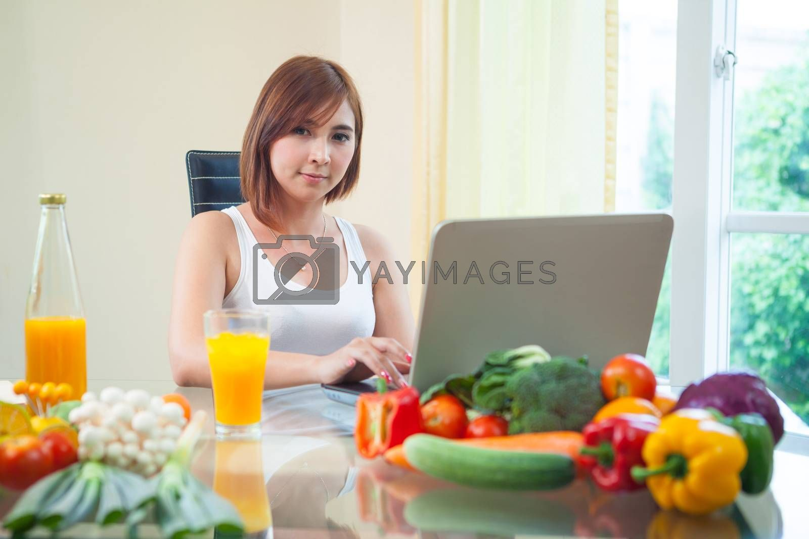 Young asian woman drinking orange juice and using internet at home