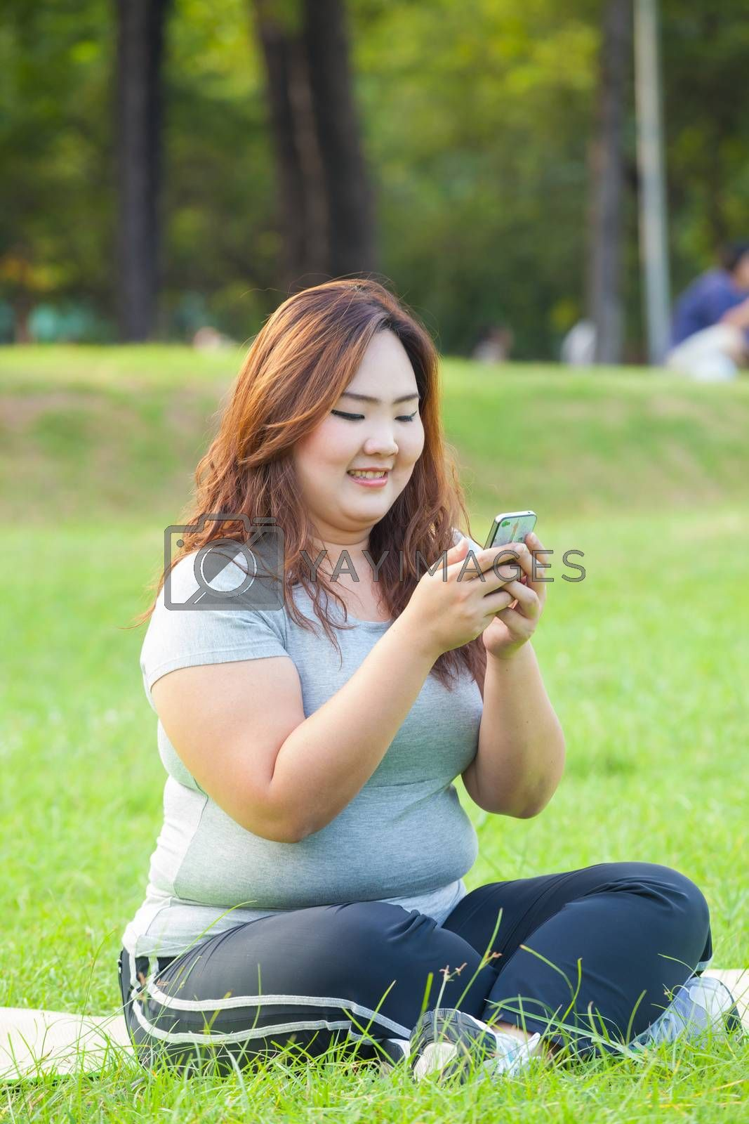 Happy fatty asian woman using mobile phone outdoor in a park