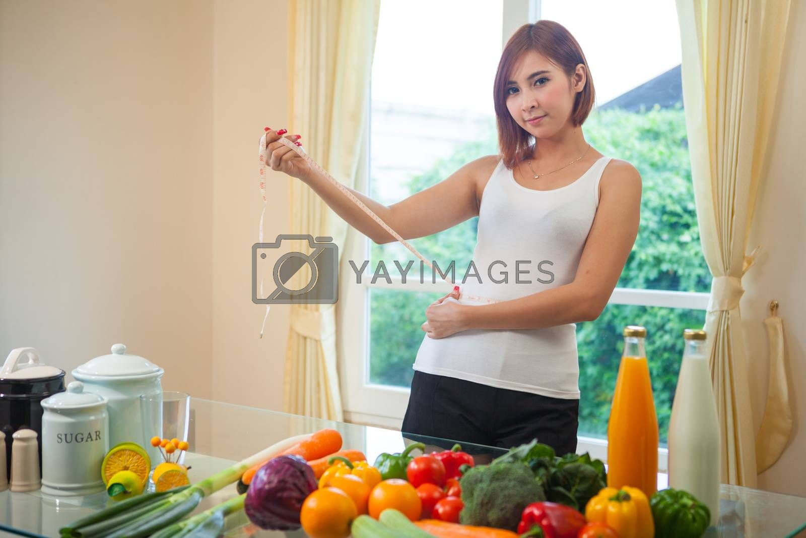 Young asian woman measuring her stomach