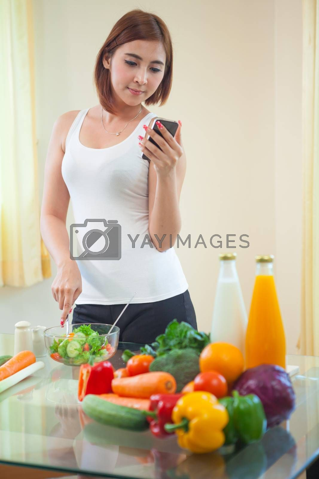 Young asian woman In Kitchen Following Recipe On Mobile phone