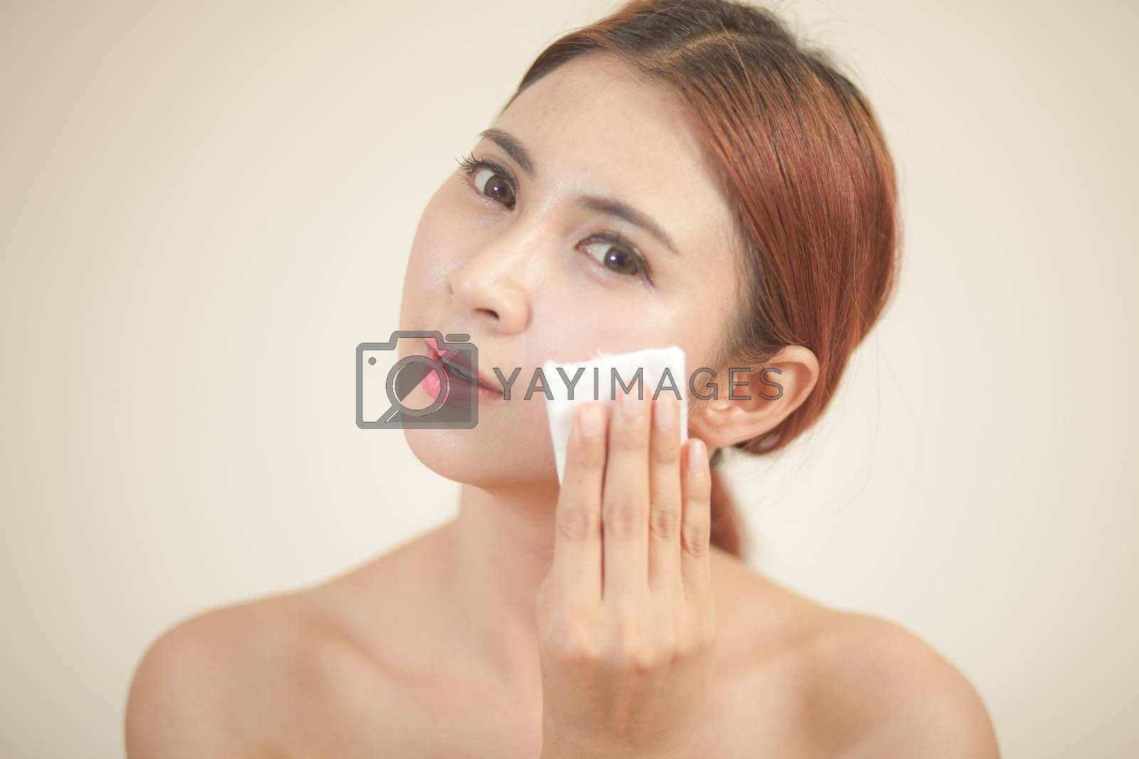A close up of a beautiful young woman removing her make up.