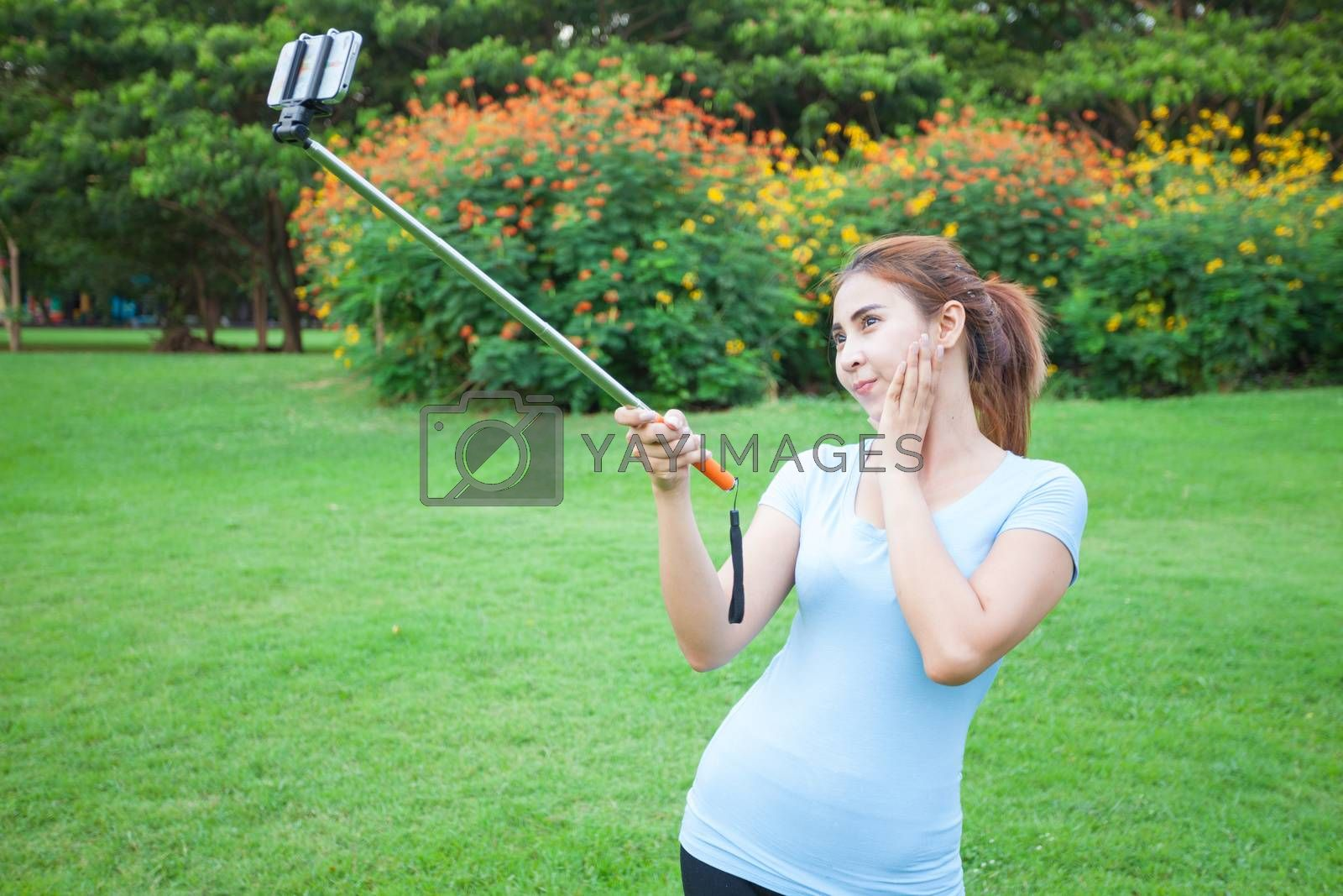 Pretty young female tourist takes travel selfie at the park