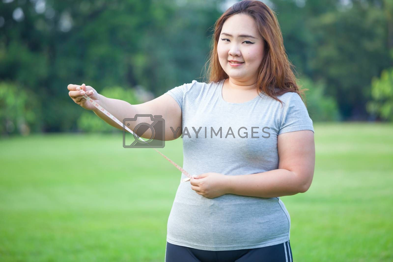 Happy fat asian woman measuring her stomach in the park