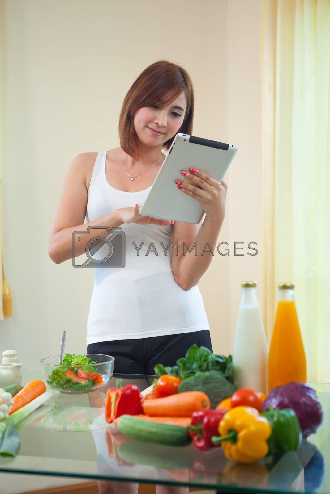 Young asian woman In Kitchen Following Recipe On Digital Tablet