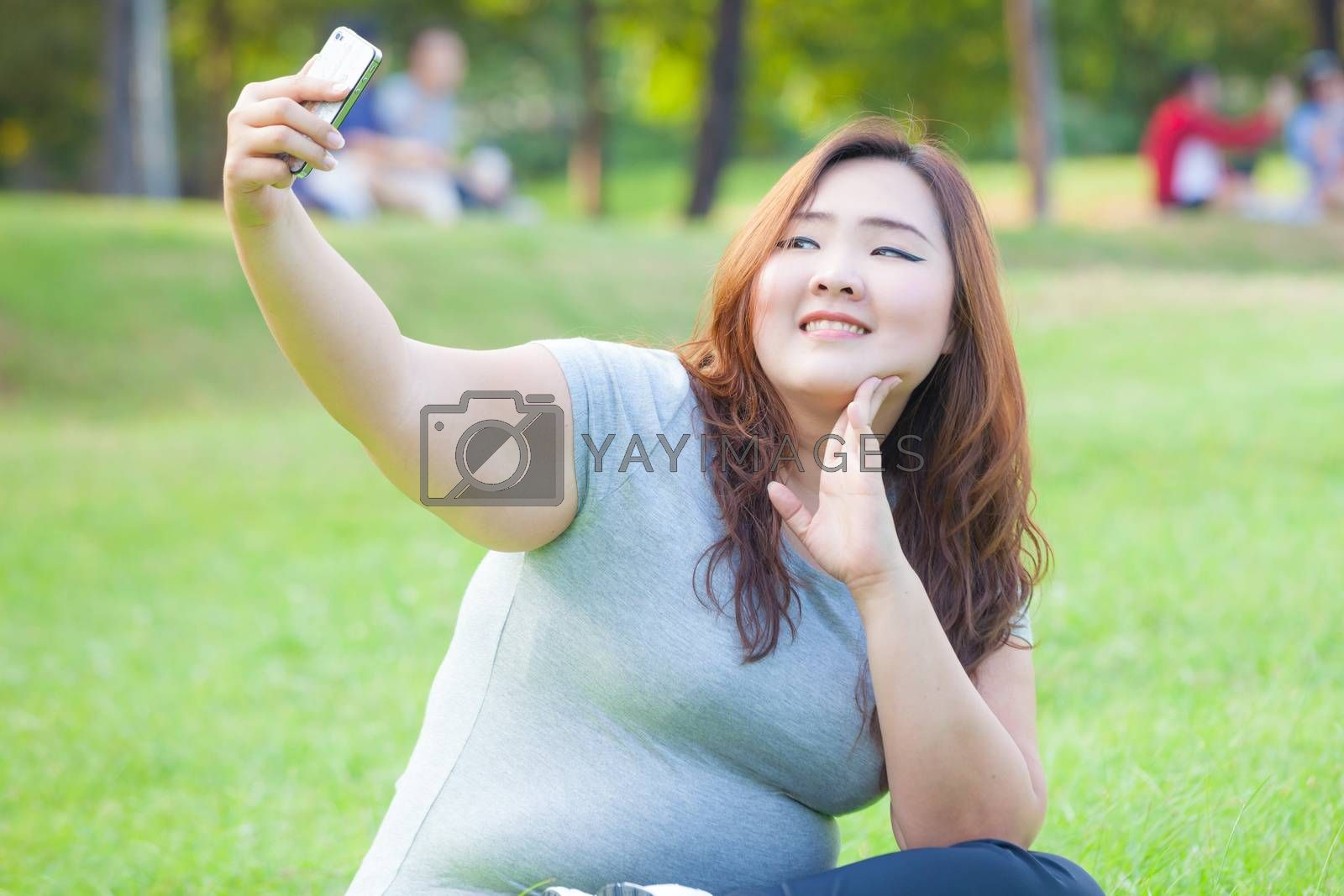 Pretty fat female takes travel selfie at the park
