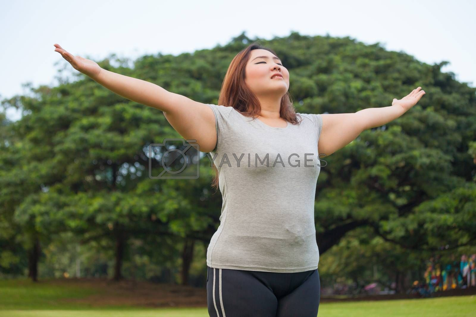 Happy fatty asian woman posing outdoor in a park