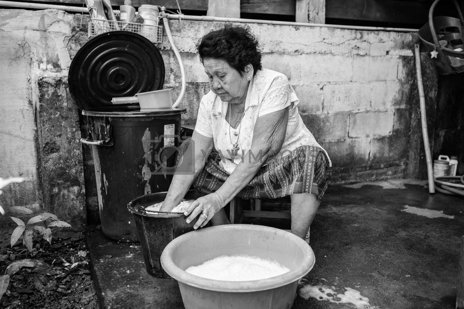 Black and white image of Senior asian woman washing cloths by hand