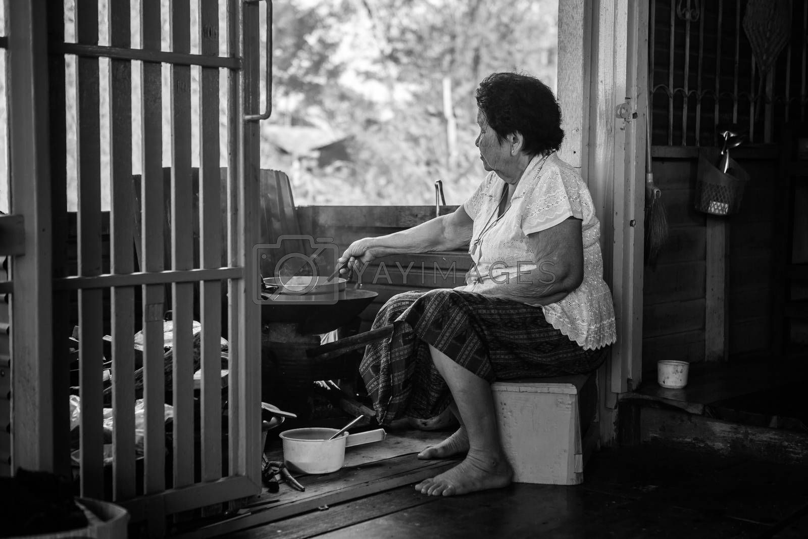 Black and white image of Senior asian woman cooking in kitchen