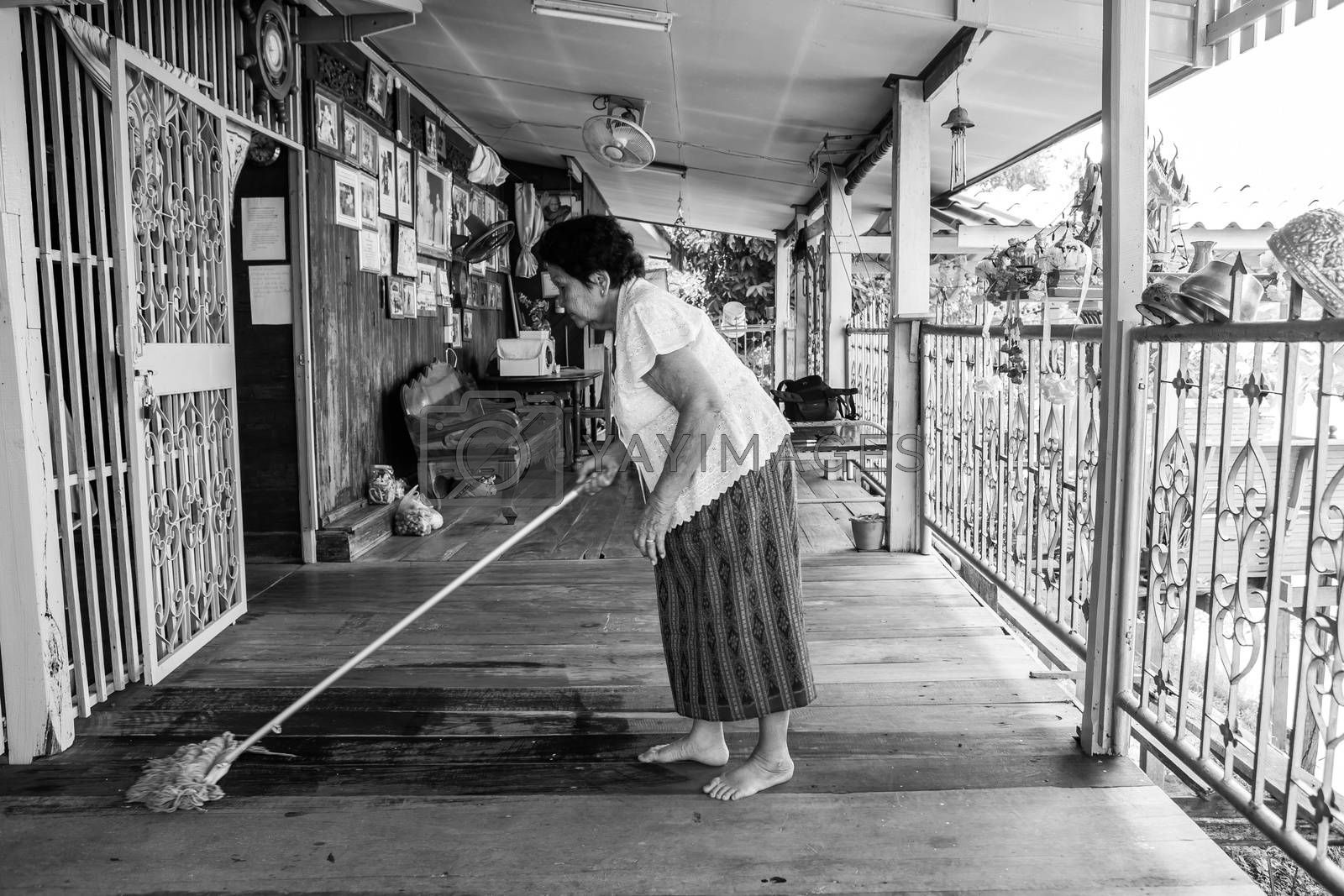 Black and white image of Senior asian woman Cleaning house