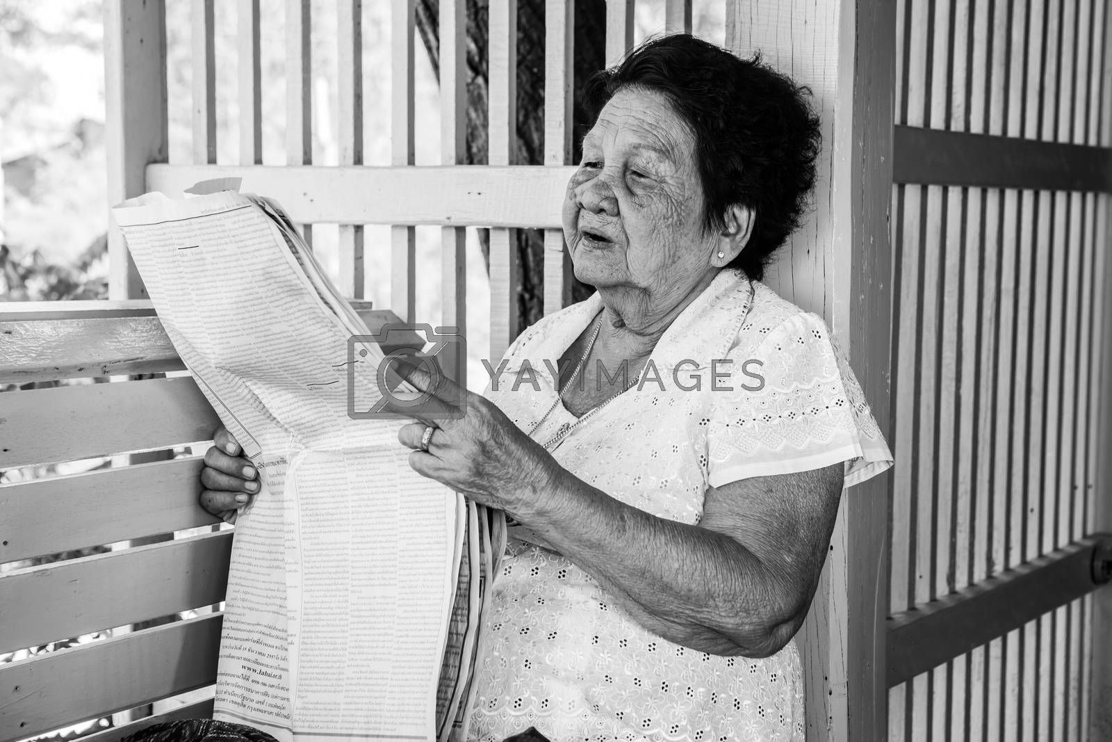Black and white image of Senior asian woman  Relaxing With Newspaper At Home