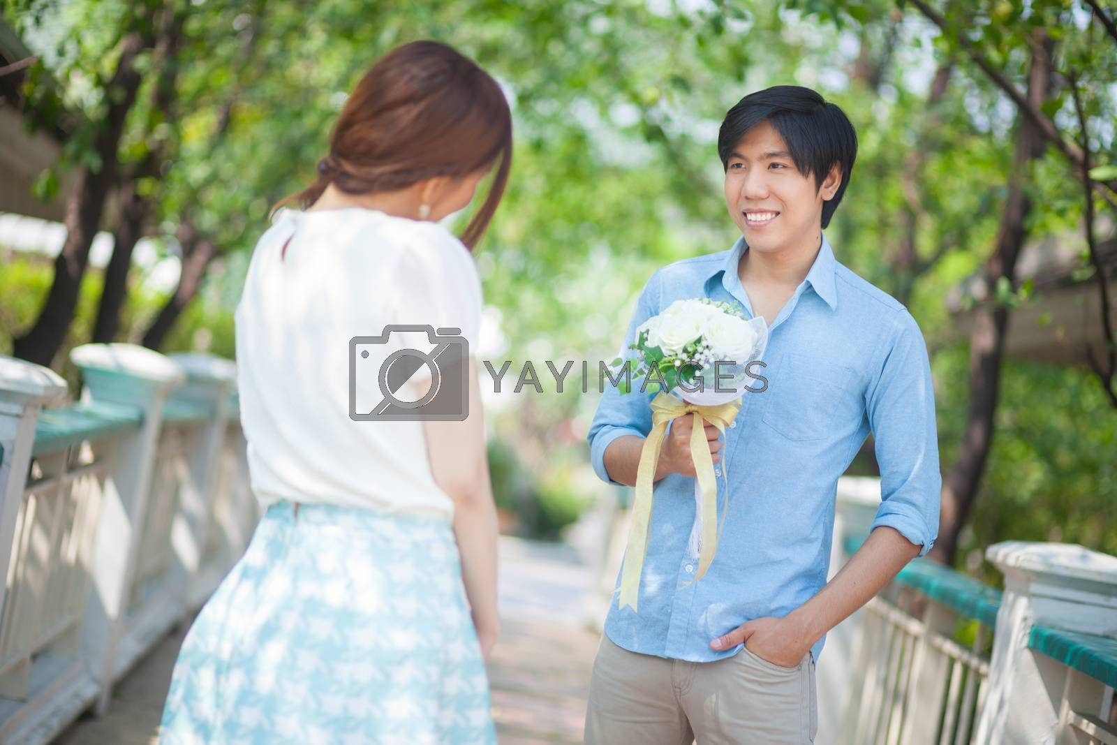 Royalty free image of Man ready to give flowers to girlfriend by witthaya