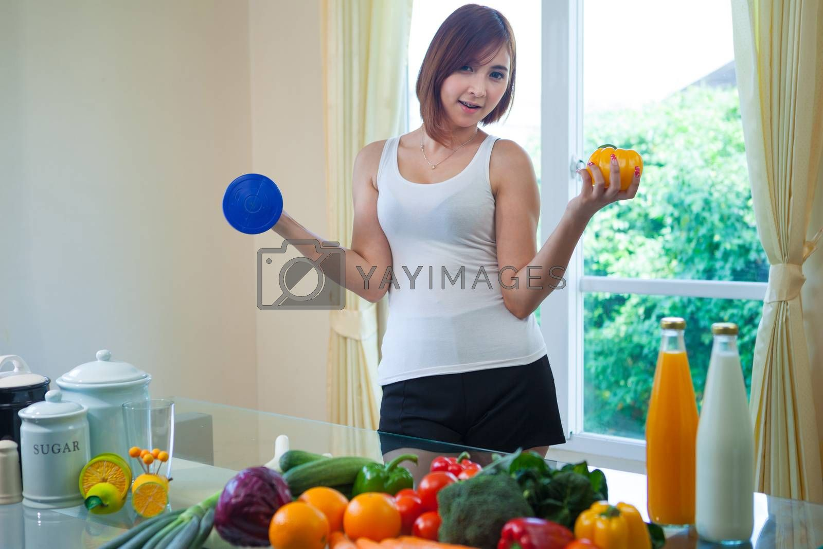 Portrait of a healthy asian woman with vegetables and dumbbell in home