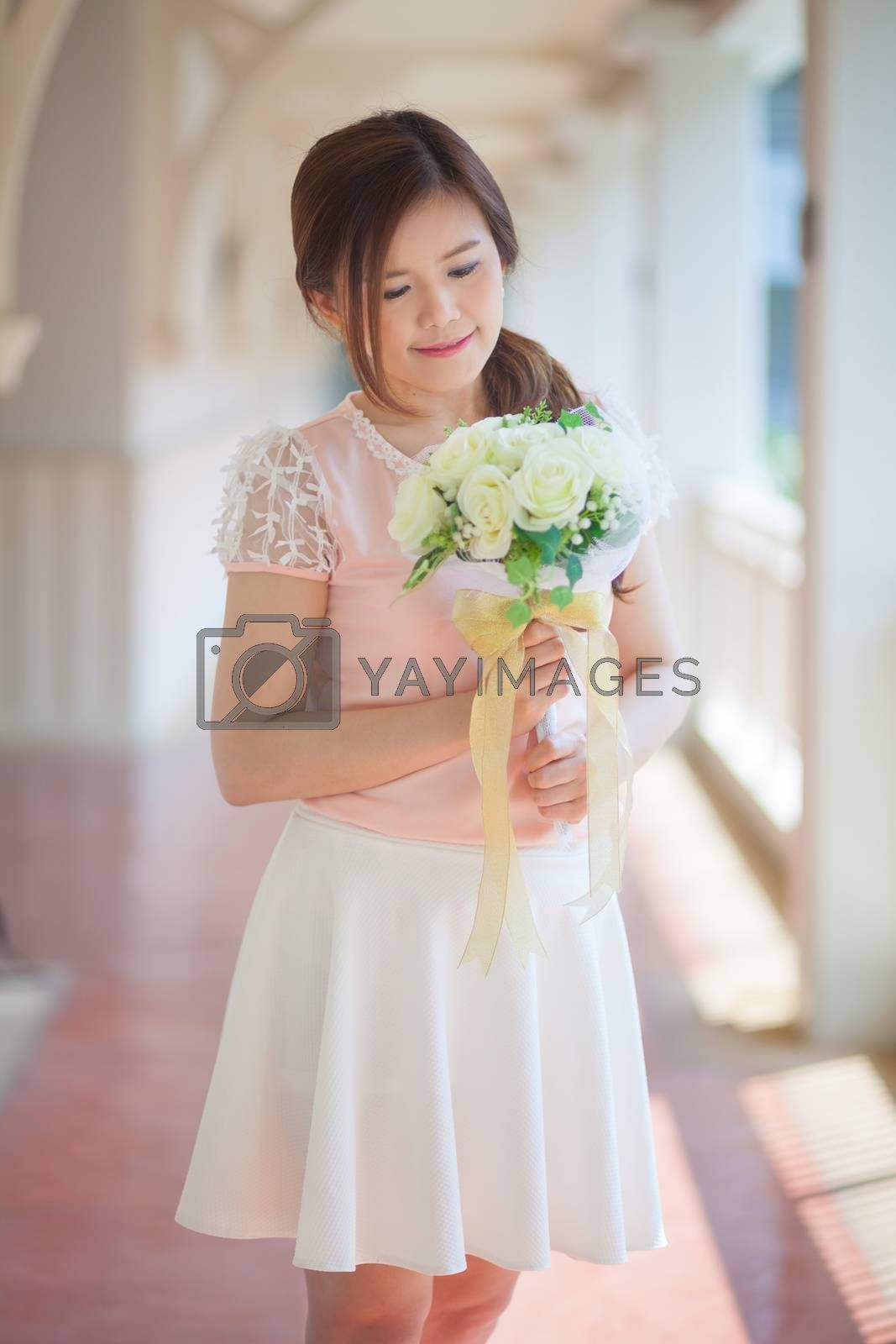Young asian cute woman smelling white flowers