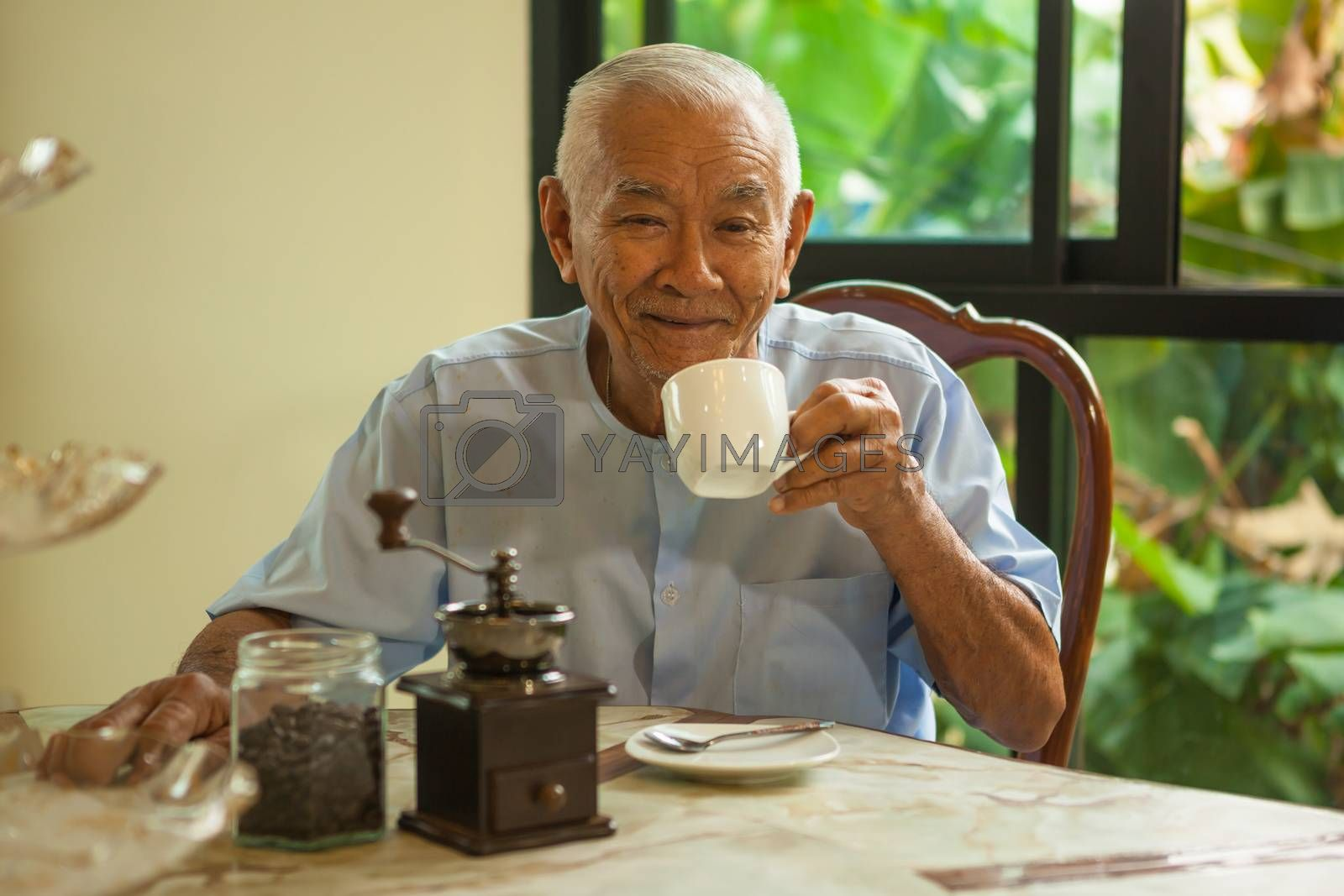 Asian senior man with vintage coffee grinder and coffee beans