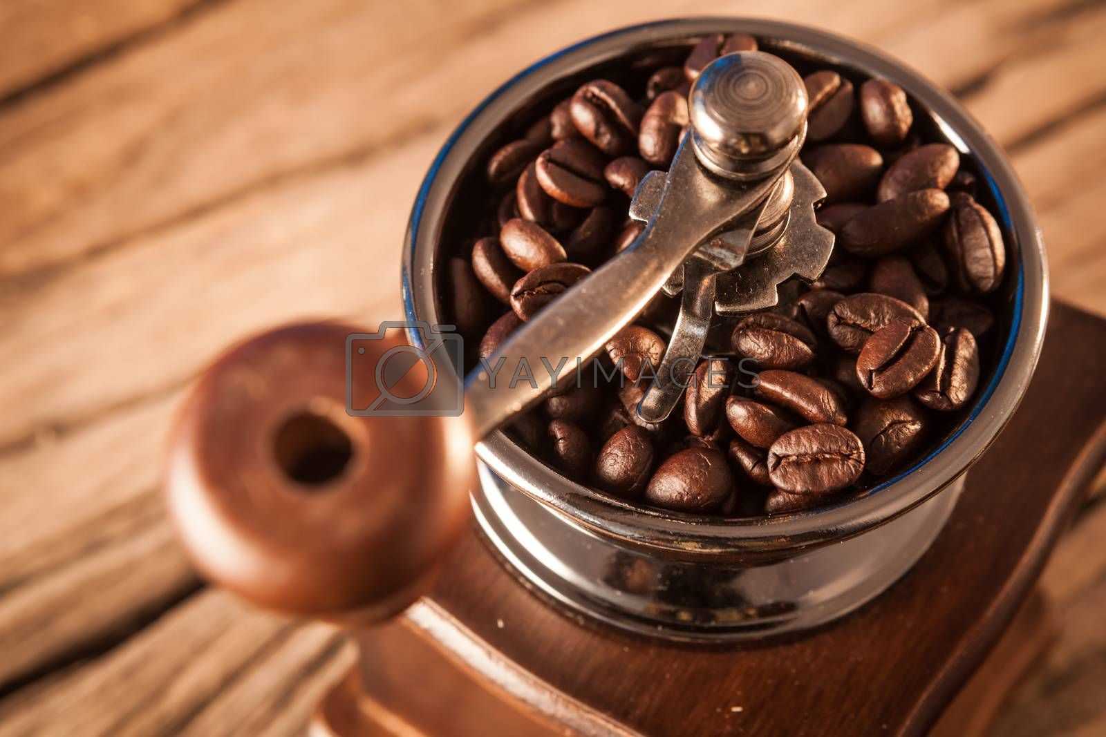 Vintage manual coffee grinder with coffee beans on wood table