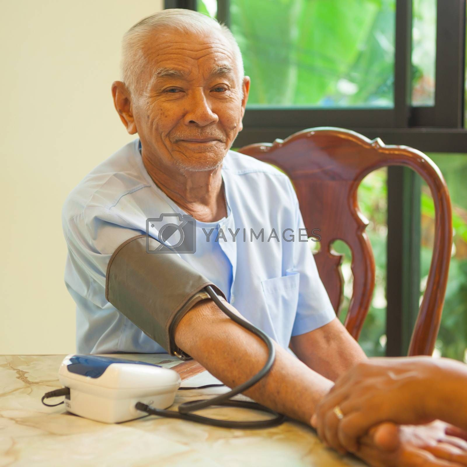 doctor measuring blood pressure of senior asian man patient