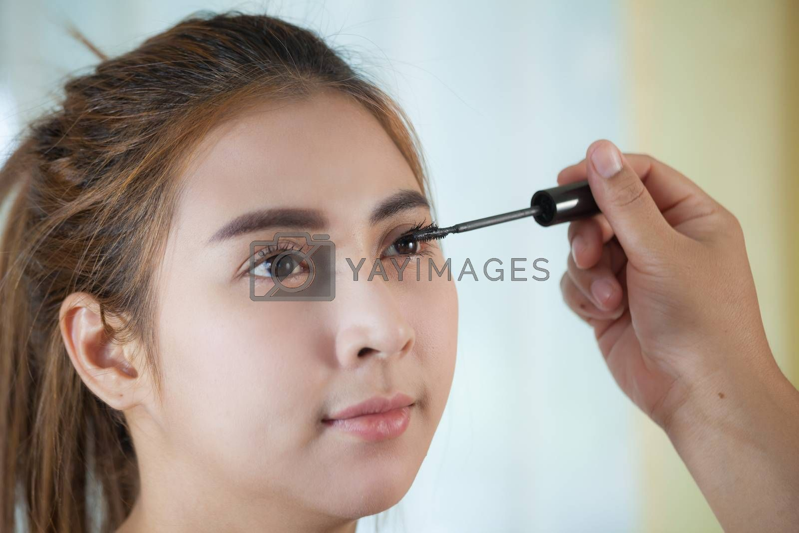 Young asian woman applying mascara on her long eyelashes