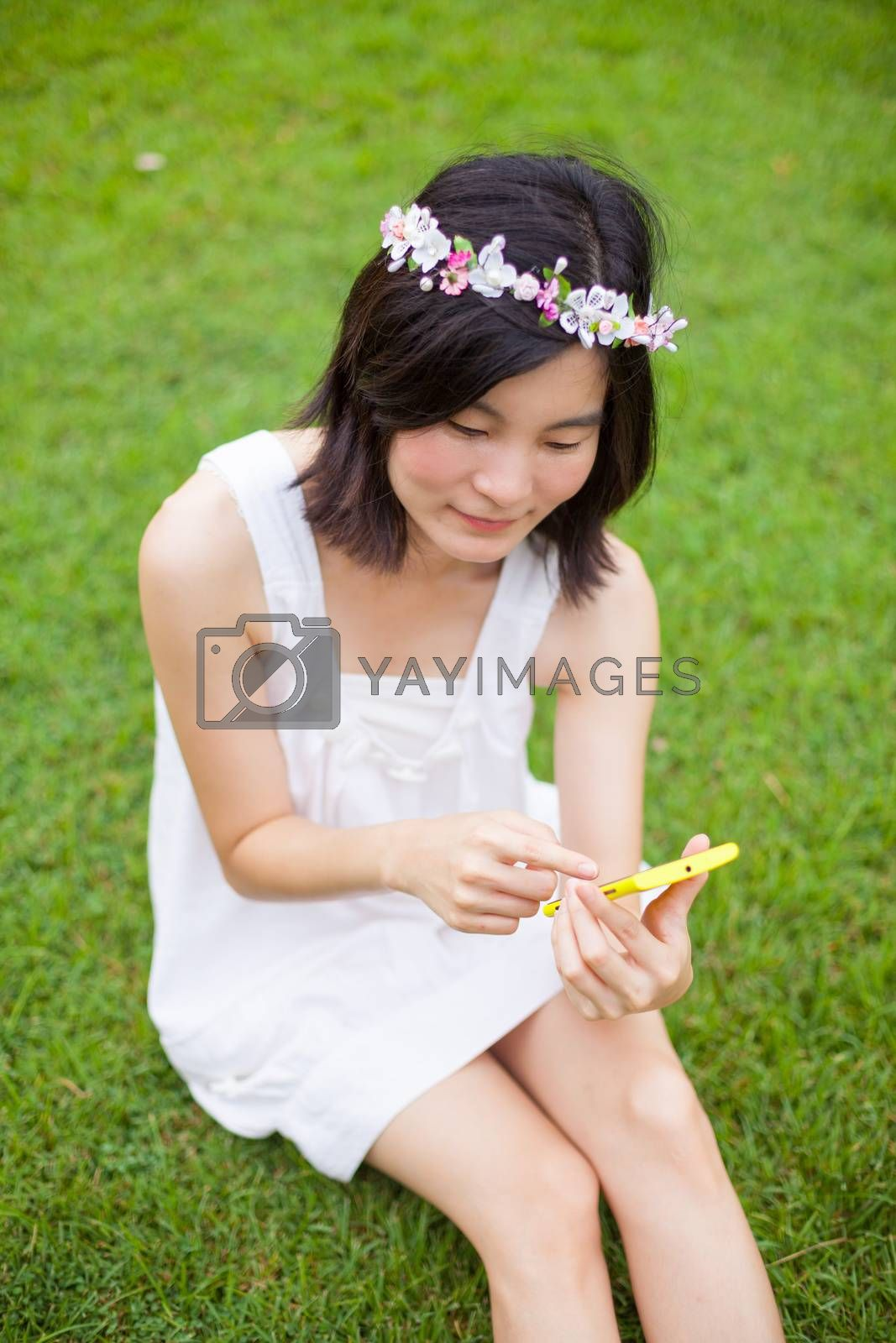 Asian woman using mobile smart phone in the park