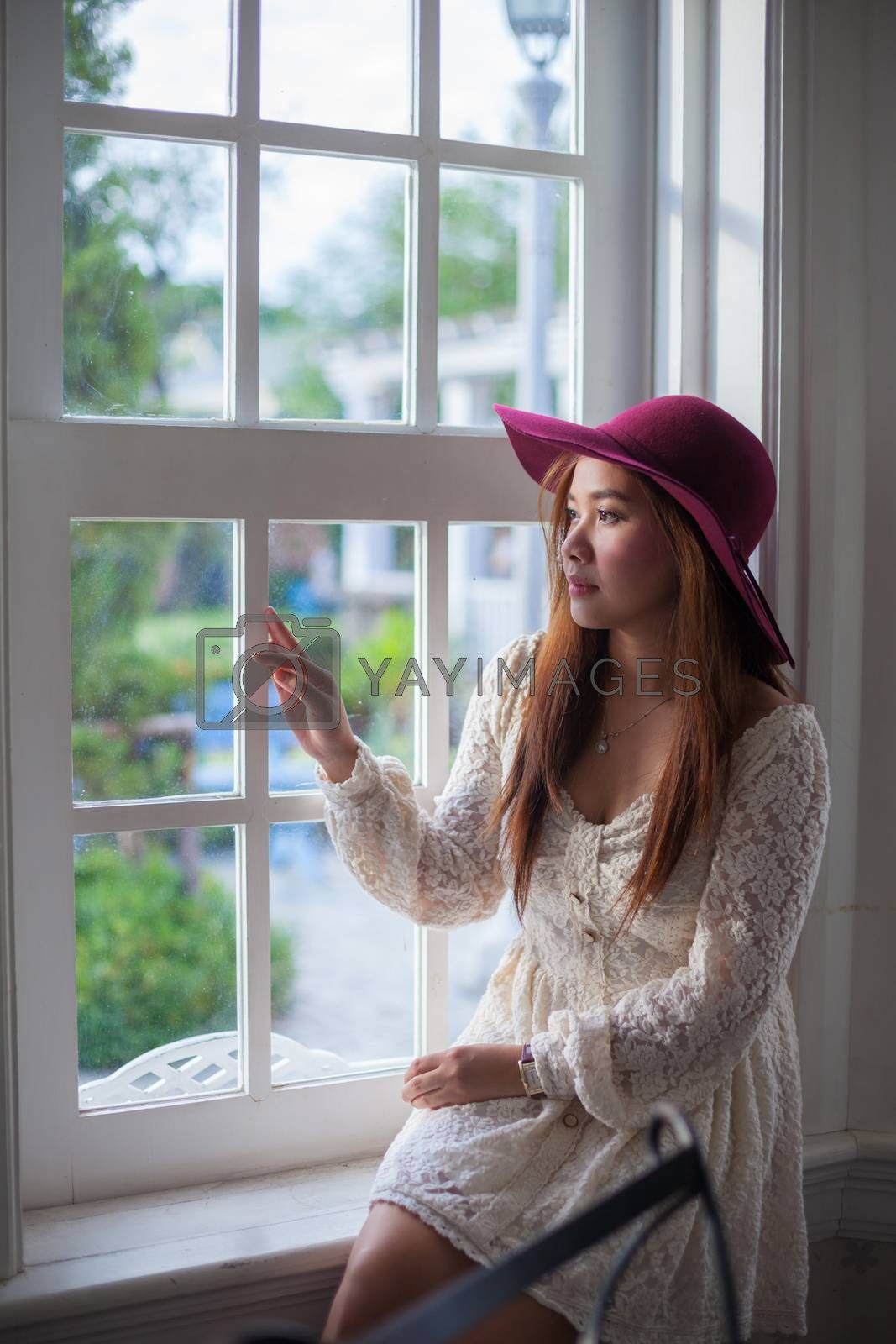 Sad asian vintage woman on the window looking out the window