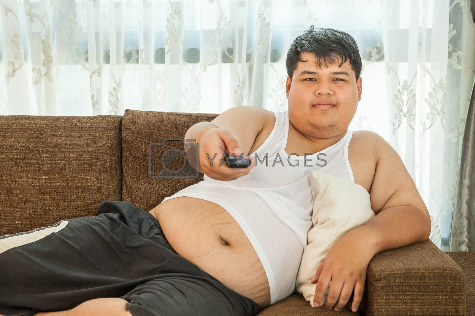Overweight guy sitting on the couch to watch some TV