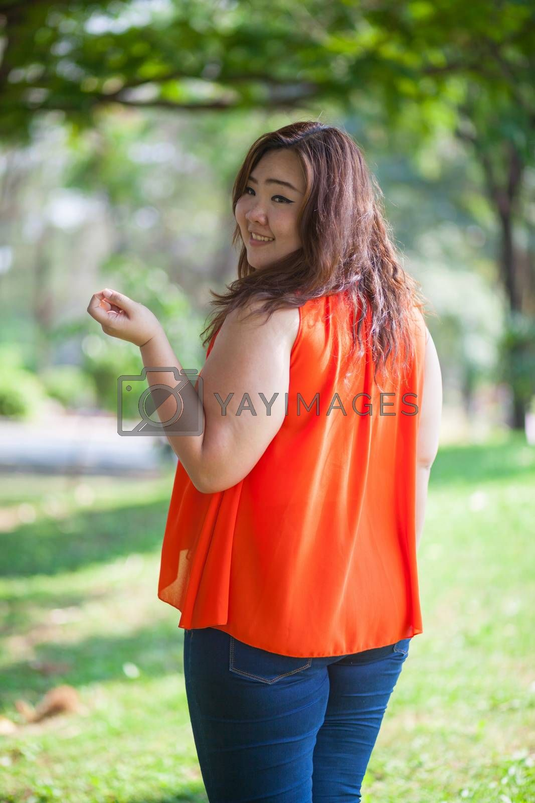 happy fatty asian woman outdoor in a park