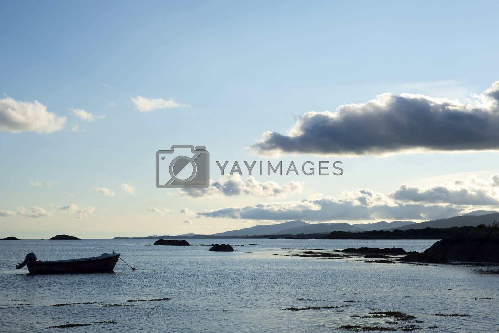 boat in a quiet bay near kenmare on the wild atlantic way ireland at blue sunset