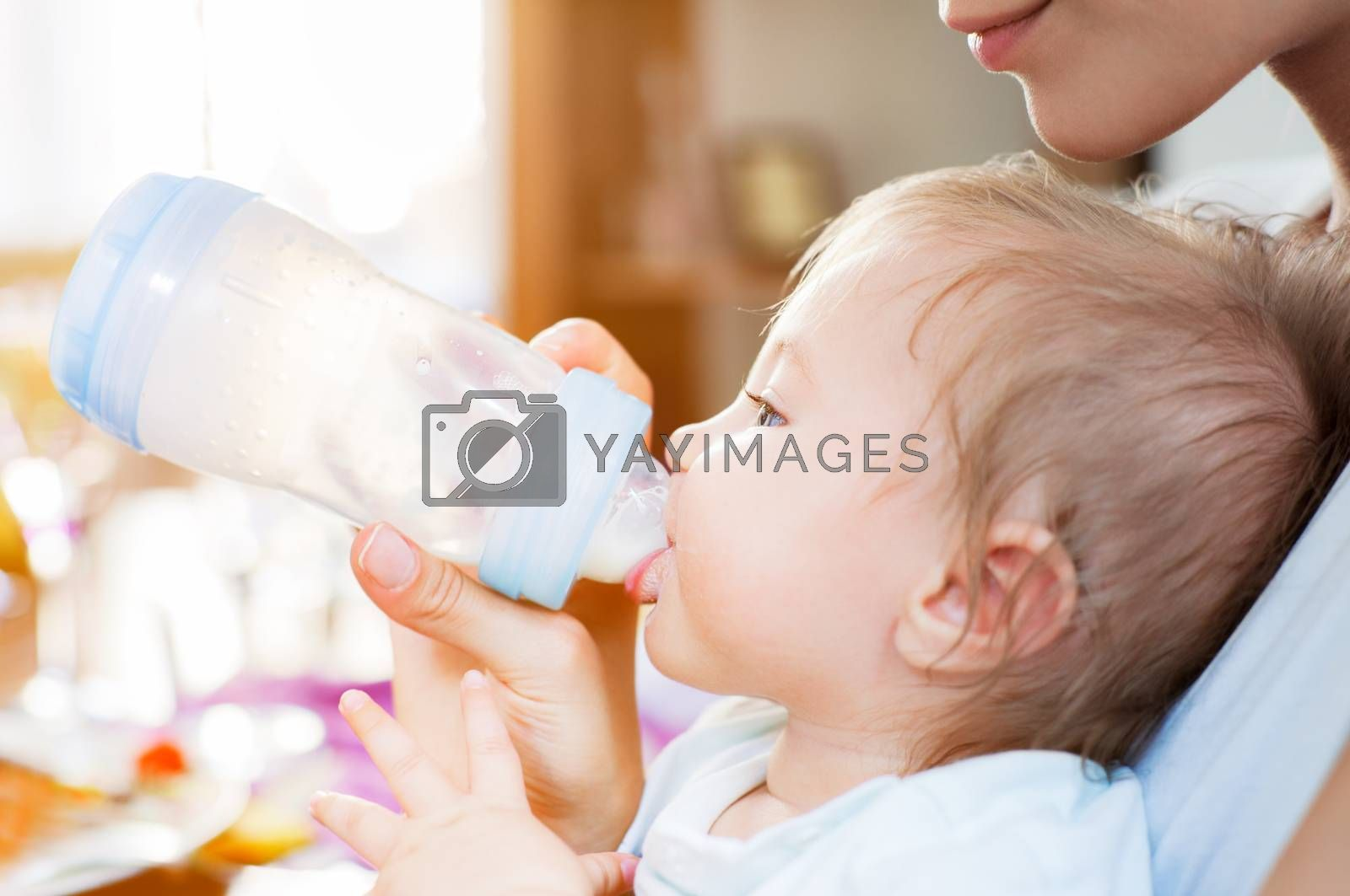 A baby boy is fed with milk from a pacifier bottle by his young mother.