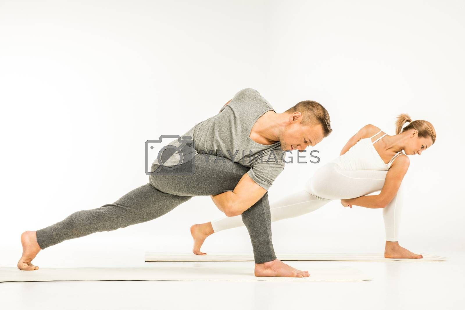 Young sportive couple practicing  variation of Revolved Side Angle Pose (Parivrtta Parsvakonasana)  on yoga mats
