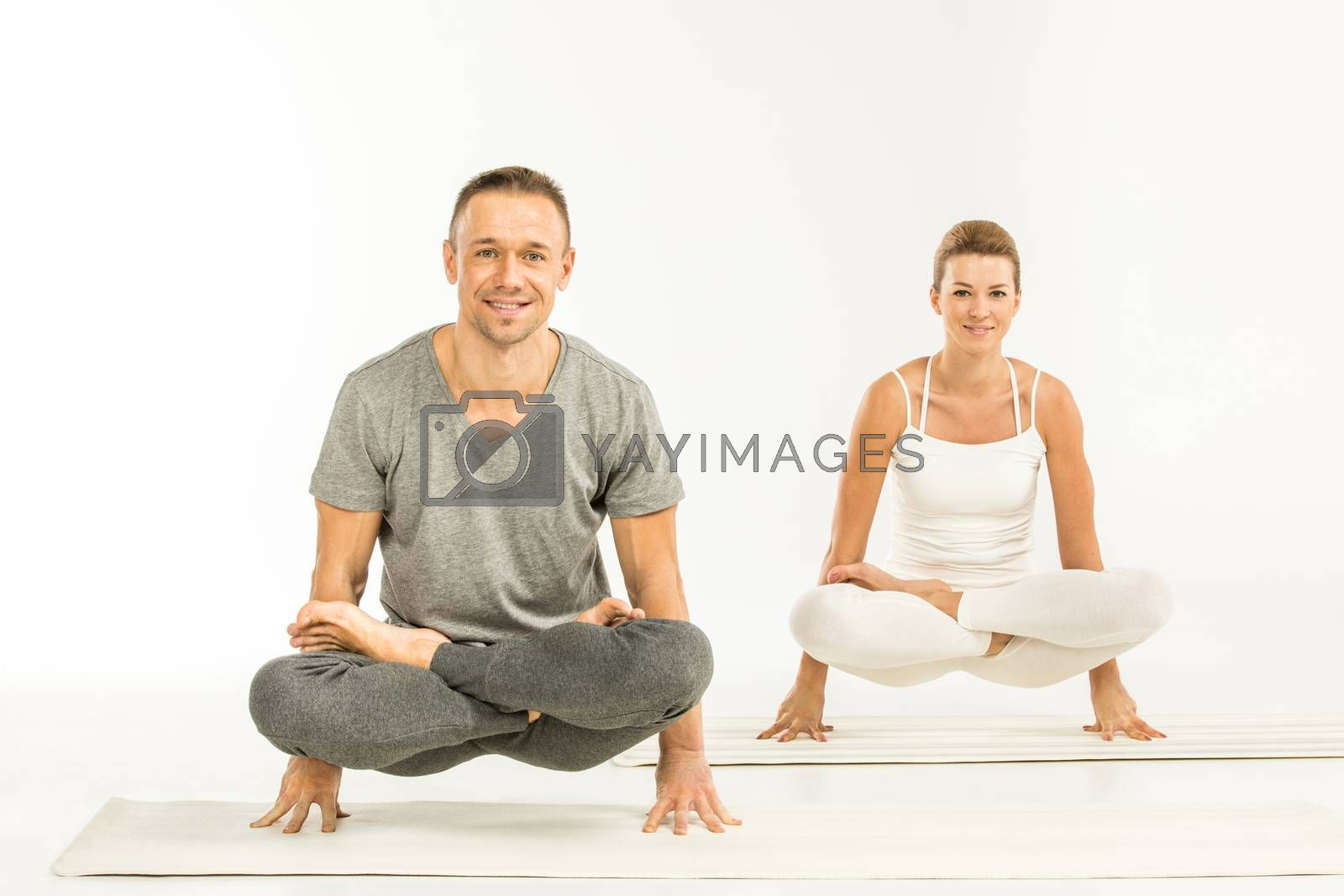 Young athletic couple practicing yoga in scale posture on yoga mat