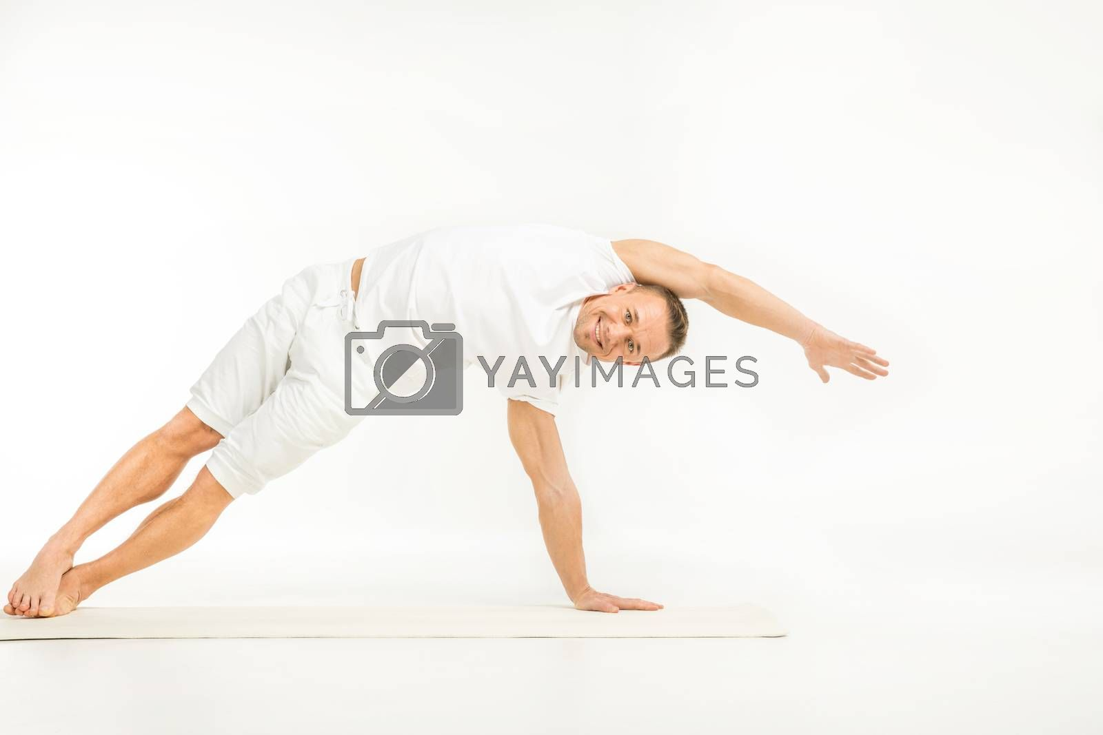 Man practicing yoga in side plank variation and smiling at camera