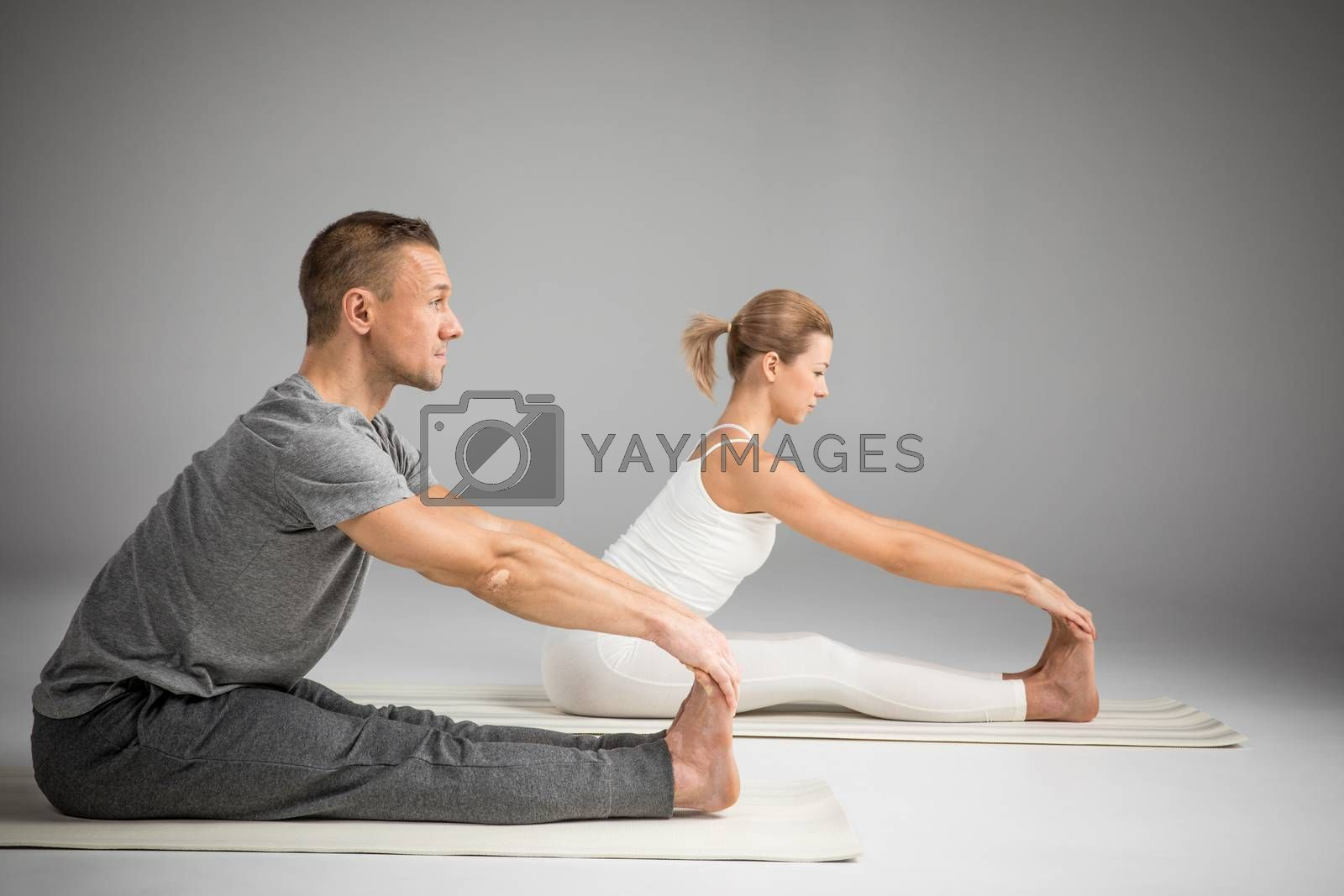 Couple practicing yoga sitting in Paschimottanasana (Seated Forward Bend) yoga position