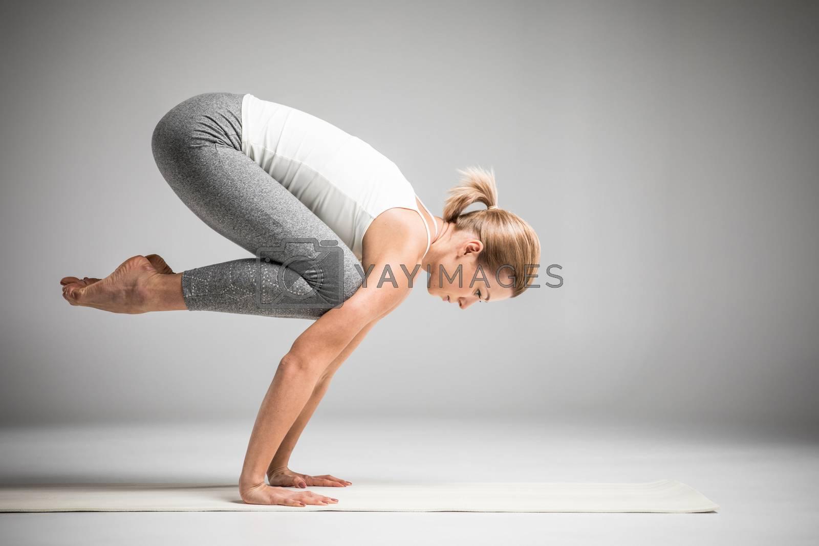 Woman practicing yoga standing in Bakasana or Crane position