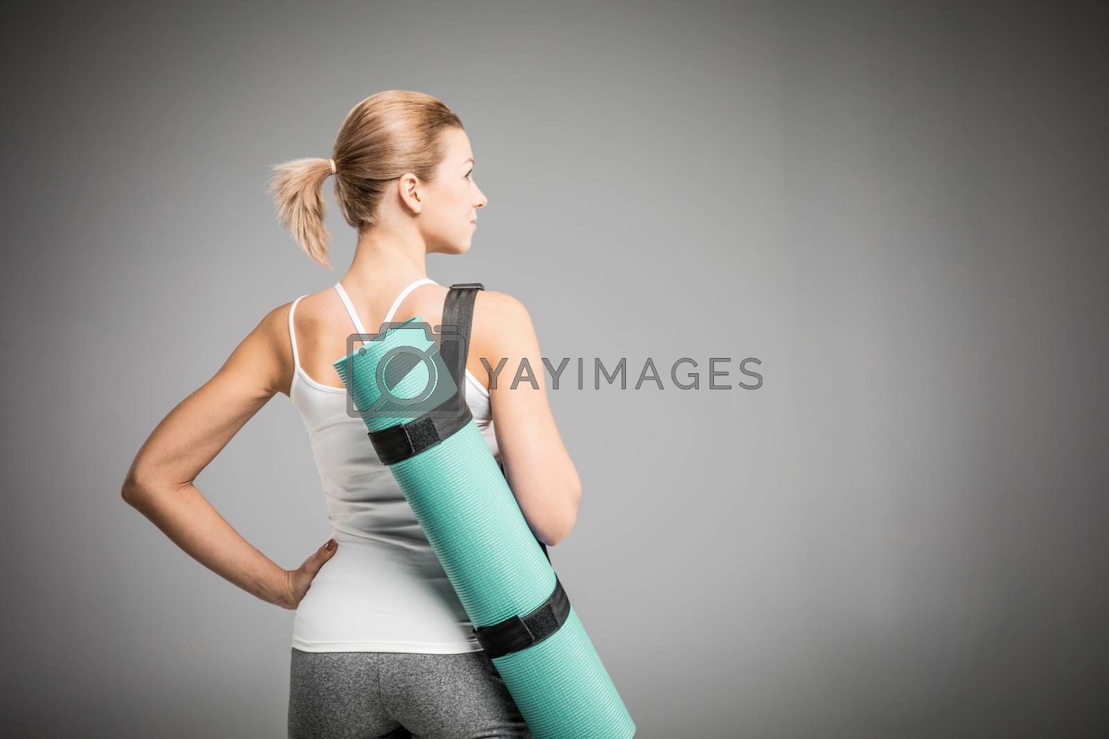 Back view of sportswoman holding yoga mat on grey