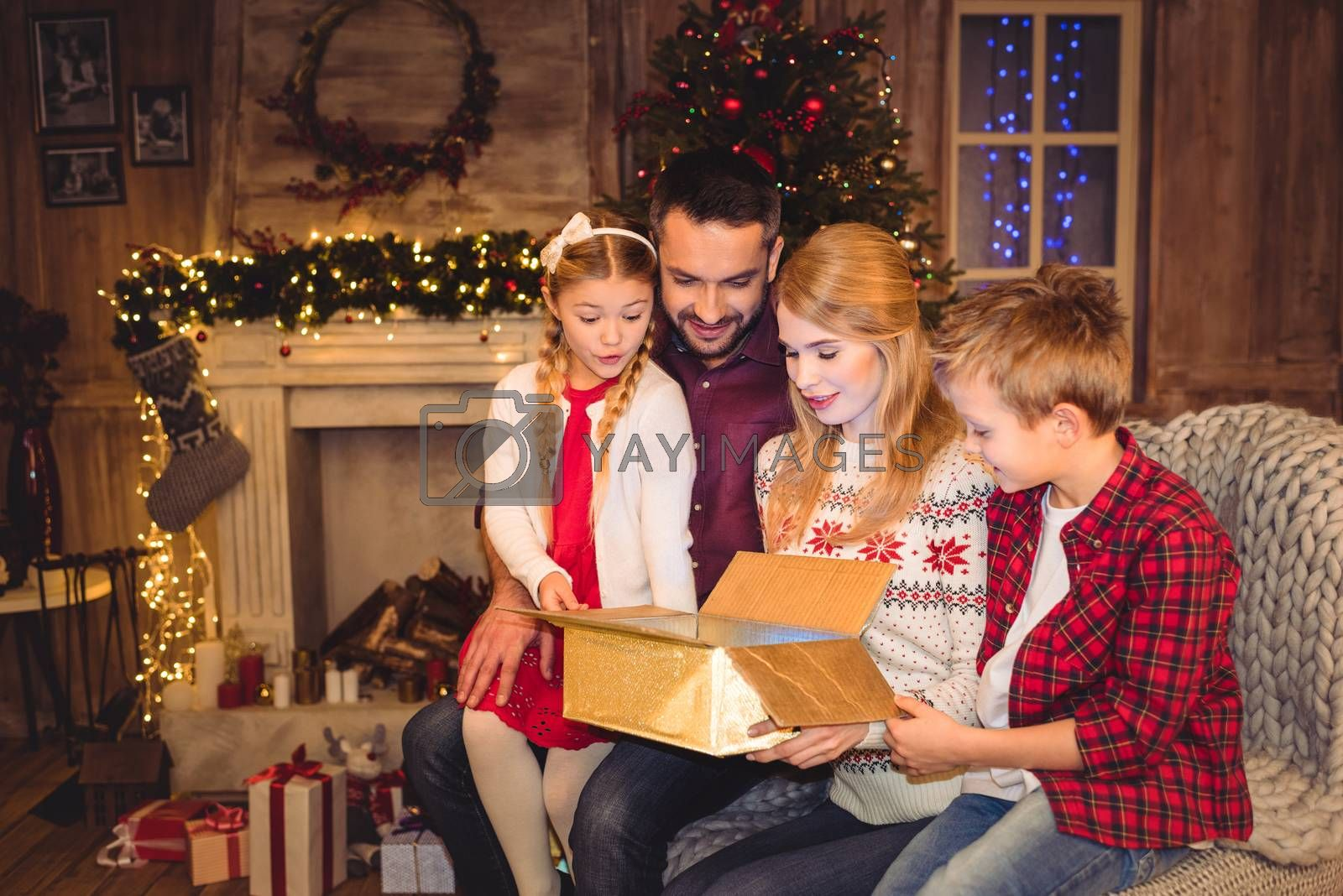 Happy family sitting together and opening gift box