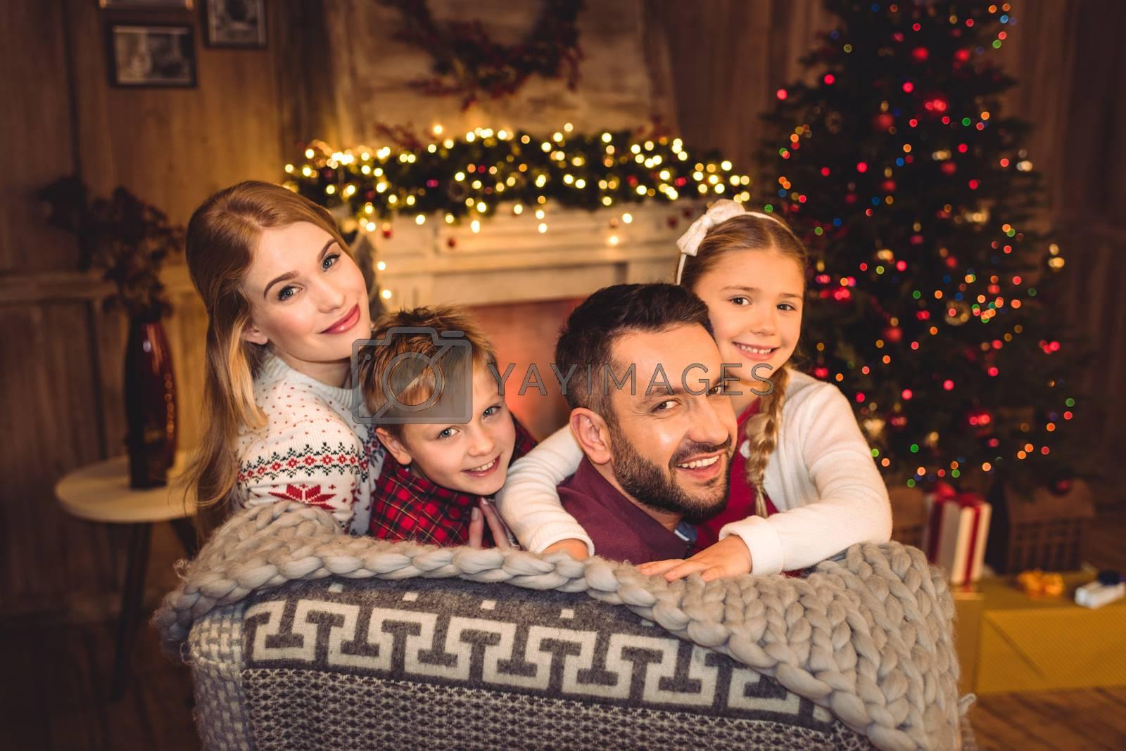 Happy family smiling at camera at christmastime