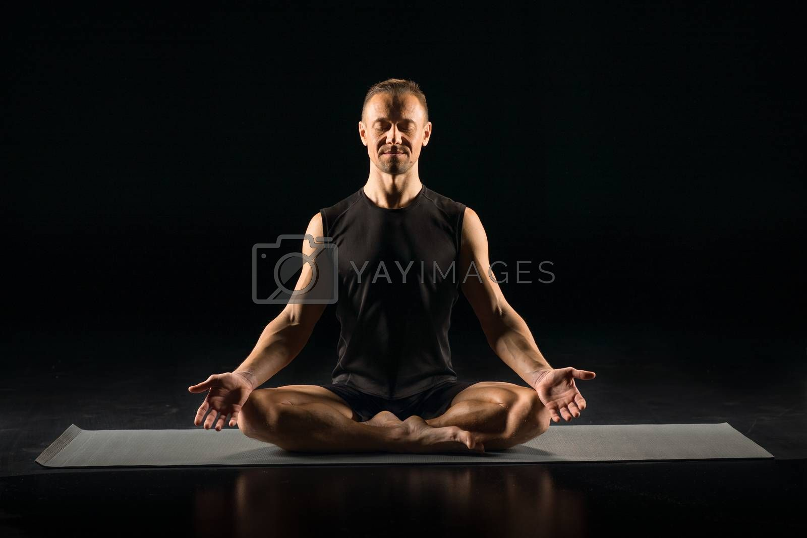 Man sitting in yoga position by LightFieldStudios