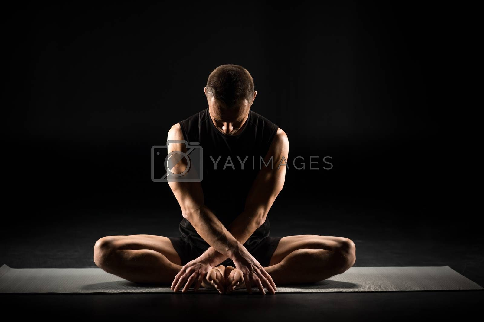 Man performing Baddha Konasana on yoga mat