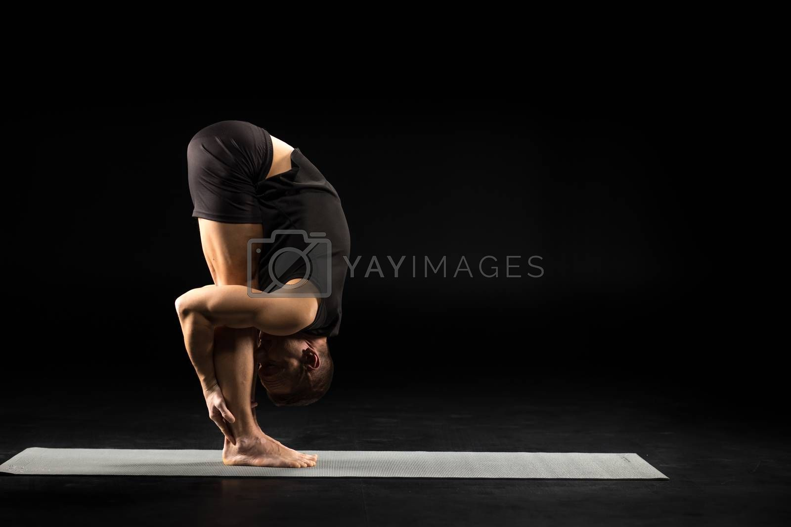 Side view of athletic man practicing yoga in Uttanasana or The Standing Forward Bend Pose