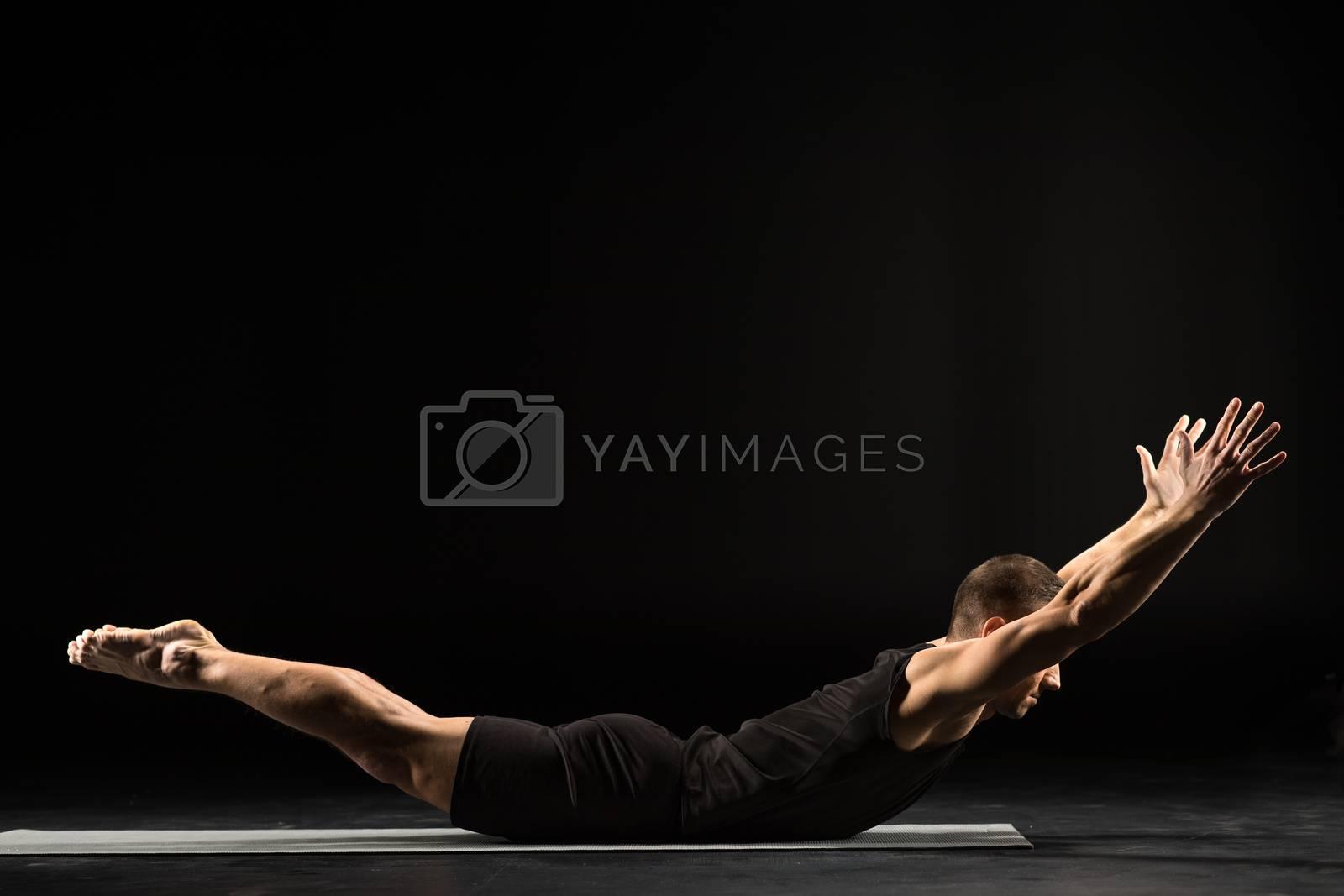 Young athletic man practicing yoga doing Naukasana The Boat Pose on yoga mat