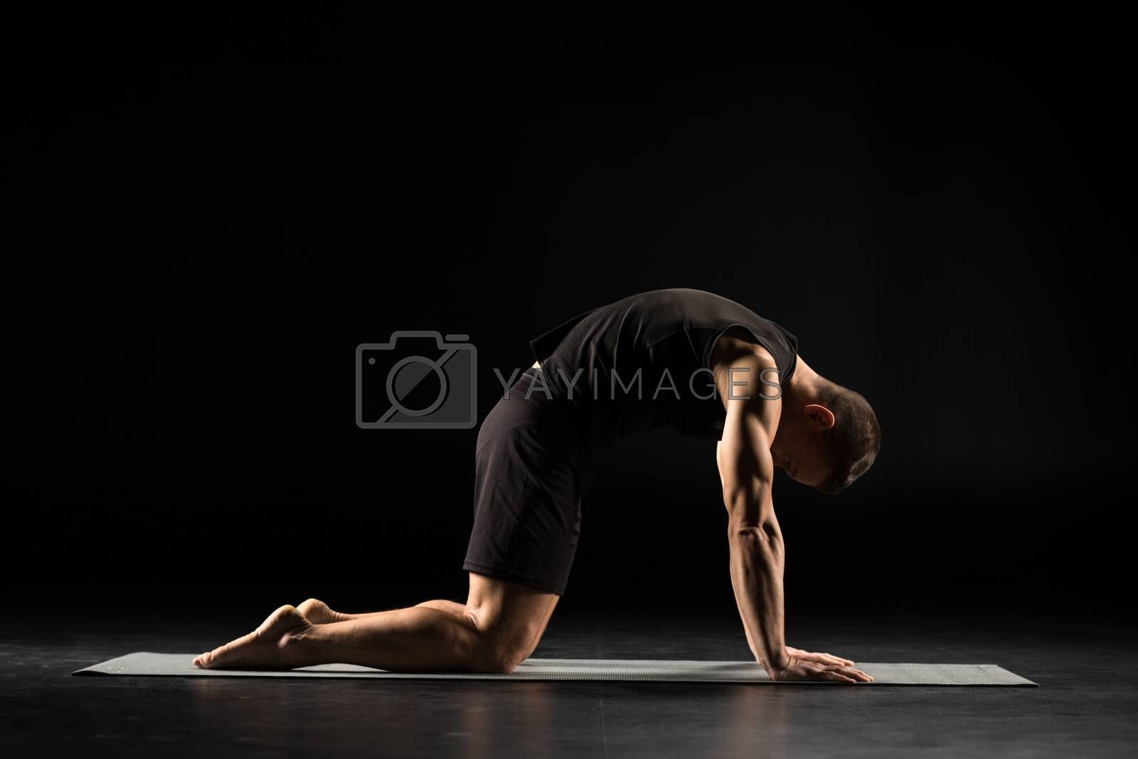 Man practicing yoga performing cat position on yoga mat